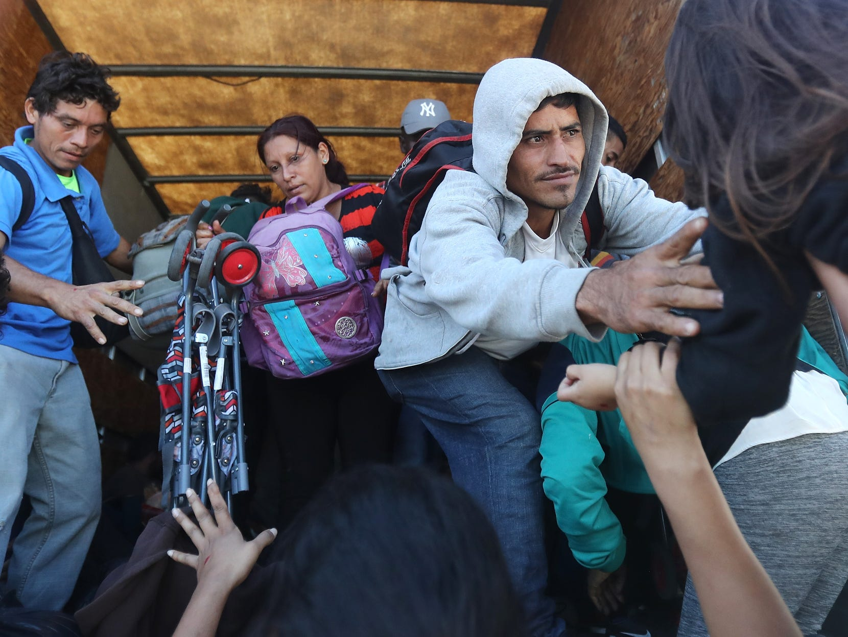 Honduran migrants from the new 'migrant caravan' climb onto the back of a truck that will drive them toward the Mexican border on Jan.17, 2019 in Guatemala City, Guatemala. A local business owner donated two trucks for migrants, saying he did so for 'the love of God'. More than one thousand Hondurans have set off toward the United States on foot or in vehicles in recent days.