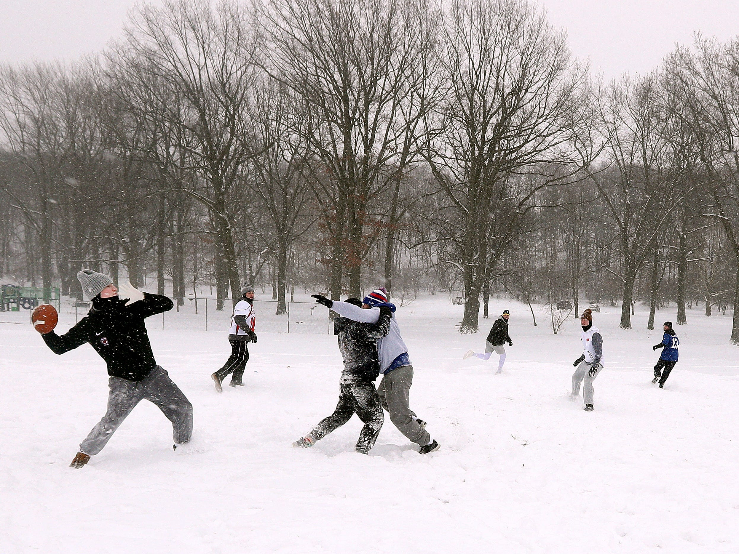 Quarterback Justin O'Dell looks to throw deep as a group of friends braved the frigid temperatures and accumulating snow to play tackle football in Cobbs Hill Park in Rochester, N.Y. on on Jan. 19, 2019.