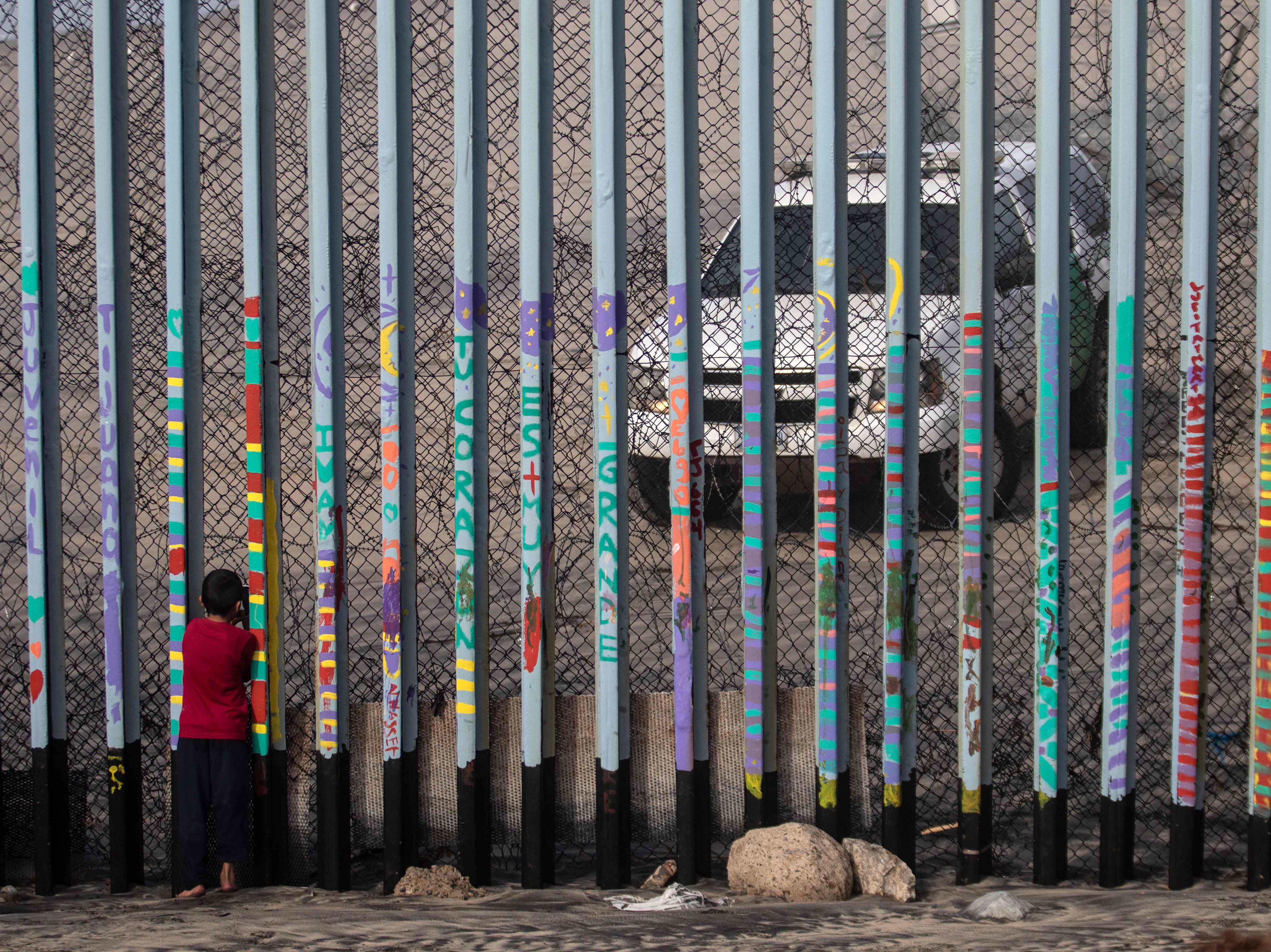 A boy looks at US border patrol guards through the US-Mexico border fence, in Tijuana, in Baja California State, Mexico, on Jan. 18, 2019. A new caravan of Central American migrants trying to reach the United States made its way across Guatemala Thursday, with the first members crossing into southern Mexico.