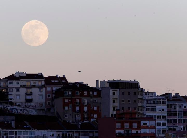 The full moon rises behind buildings on the top of a hill Sunday, Jan. 20 2019, in Lisbon. Sunday night, the Earth will slide directly between the moon and the sun, creating a total lunar eclipse. It will also be the year's first supermoon, when a full moon appears a little bigger and brighter thanks to its slightly closer position.