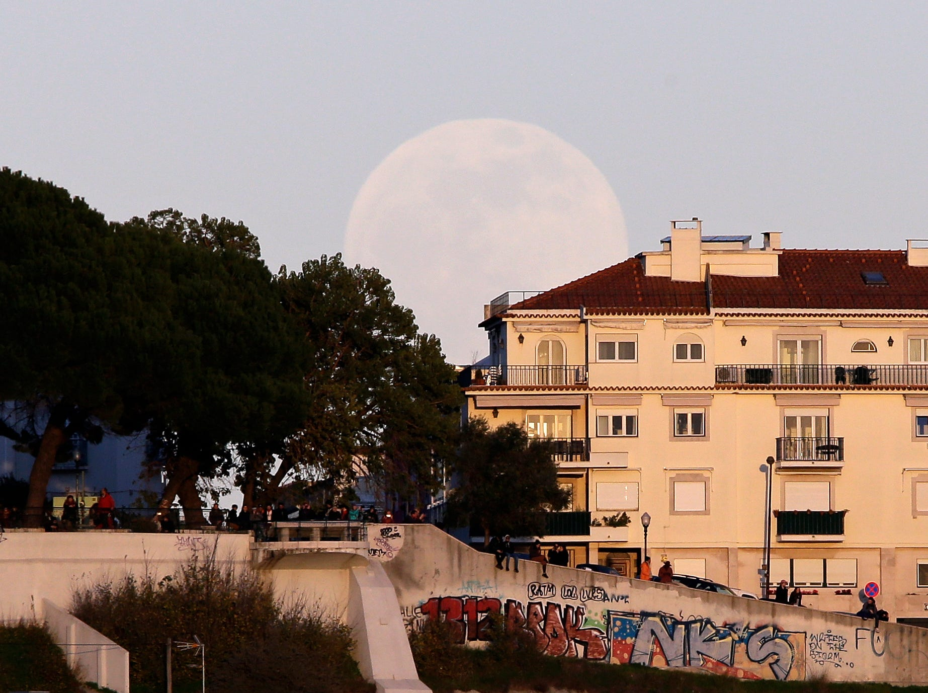 People watch the sunset from the top of a hill as the full moon rises behind them Sunday, Jan. 20 2019, in Lisbon. Sunday night, the Earth will slide directly between the moon and the sun, creating a total lunar eclipse. It will also be the year's first supermoon, when a full moon appears a little bigger and brighter thanks to its slightly closer position. (AP Photo/Armando Franca)
