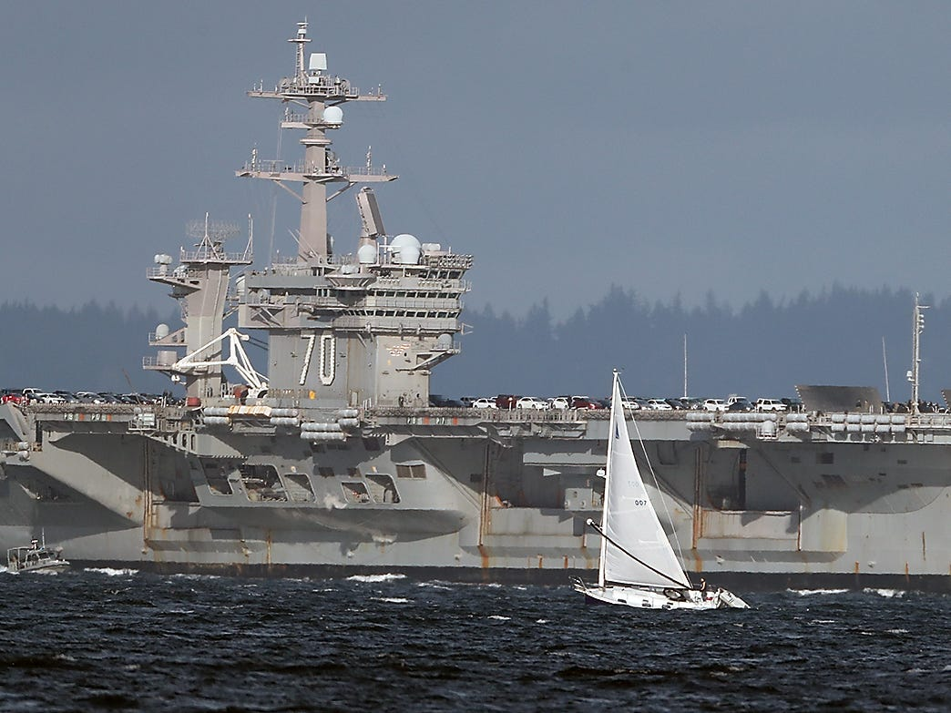 A sailboat travels past the USS Carl Vinson as it makes its way to Naval Base Kitsap Bremerton, as seen from Bainbridge Island's Rockaway Beach on Sunday, January 20, 2019.