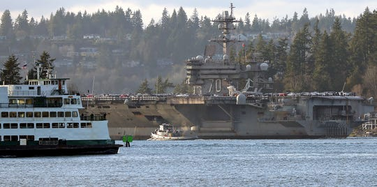 The USS Carl Vinson turns the tight corner as it makes its way through Rich Passage as seen from Bainbridge Island's Fort Ward on Sunday.