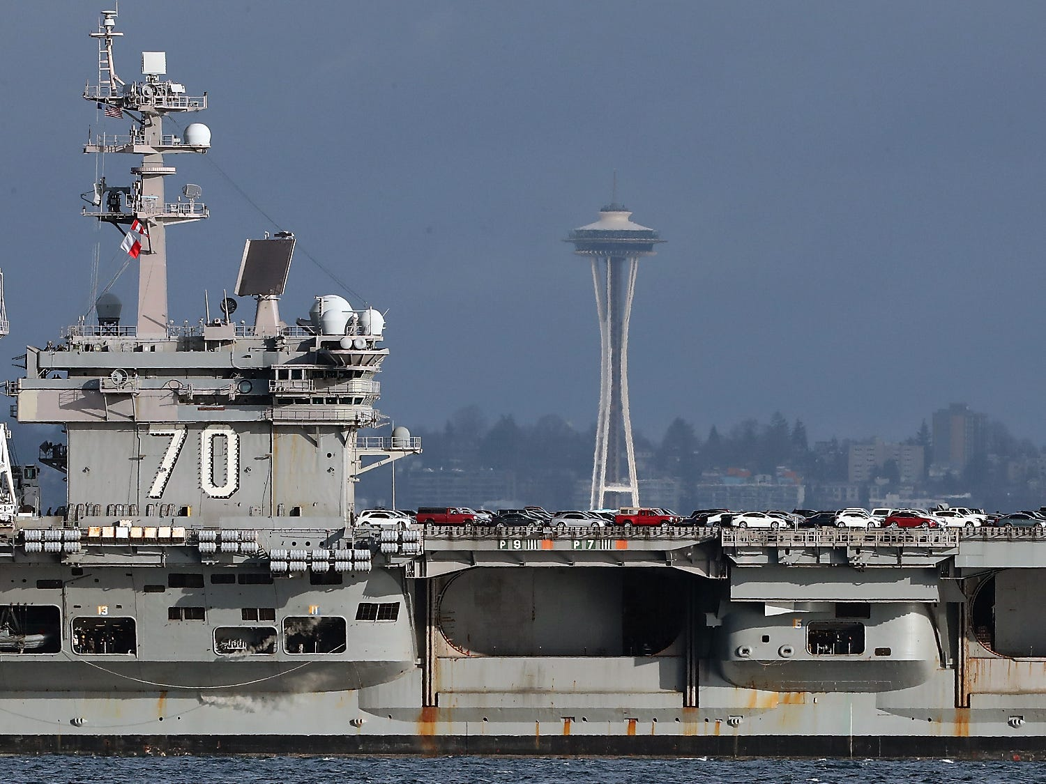 Cars fill the flight deck as the USS Carl Vinson travels past the Space Needle as seen from Bainbridge Island's Rockaway Beach on Sunday, January 20, 2019.