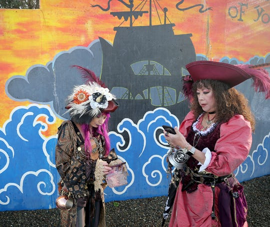 Beverly Stuart, left, of Kenmore, and Alison Alexander of Bainbridge Island check out their cell phone photos at Port Orchard's Waterfront Park as part of the A Pirate's Life For Us festival on Saturday,  January 19, 2019.