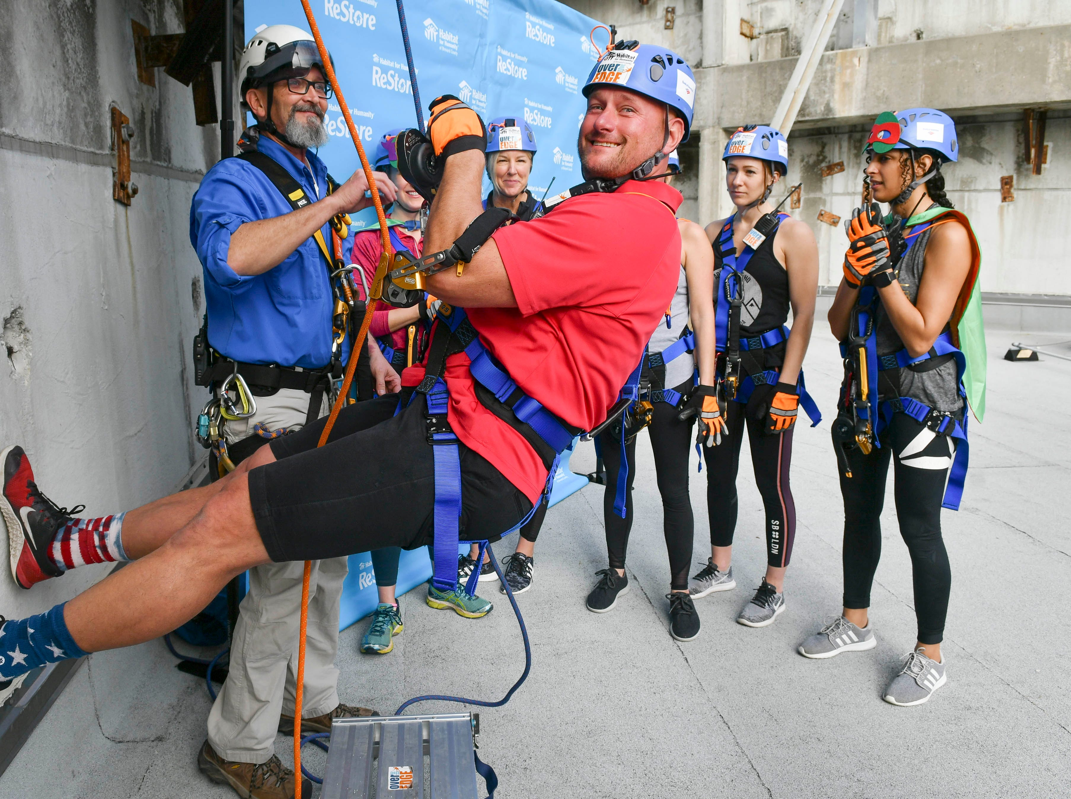 Dan Coe gets instruction from Jeff Martin before he goes Over the Edge at the Melbourne Rialto Hilton on Saturday morning. Over the Edge is a fundraiser for Habitat Humanity of Brevard, an organization that helps low-income families buy affordable houses. Teams and individuals raised money for the chance to rappel eight stories down the Hilton.