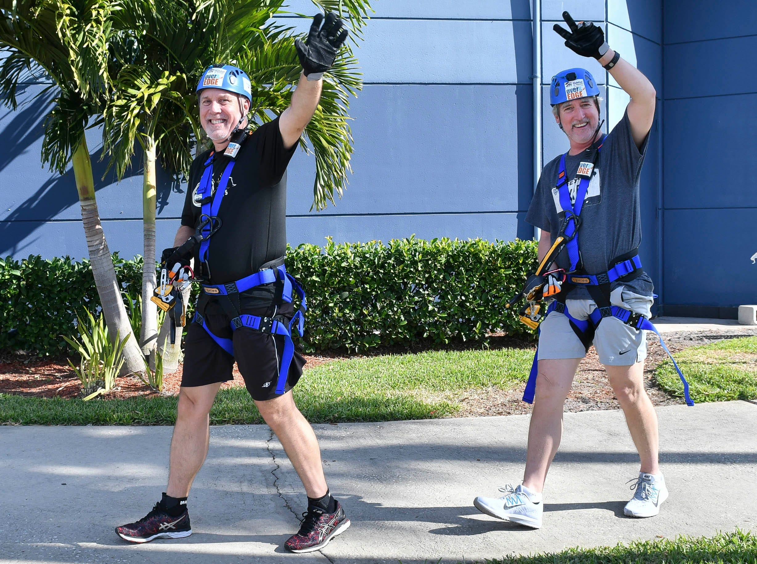 Rob and Scott Raines wave to onlookers after participating in the Over the Edge fundraiser at the Melbourne Rialto Hilton on Saturday morning. Over the Edge is a fundraiser for Habitat Humanity of Brevard, an organization that helps low-income families buy affordable houses. Teams and individuals raised money for the chance to rappel eight stories down the Hilton.
