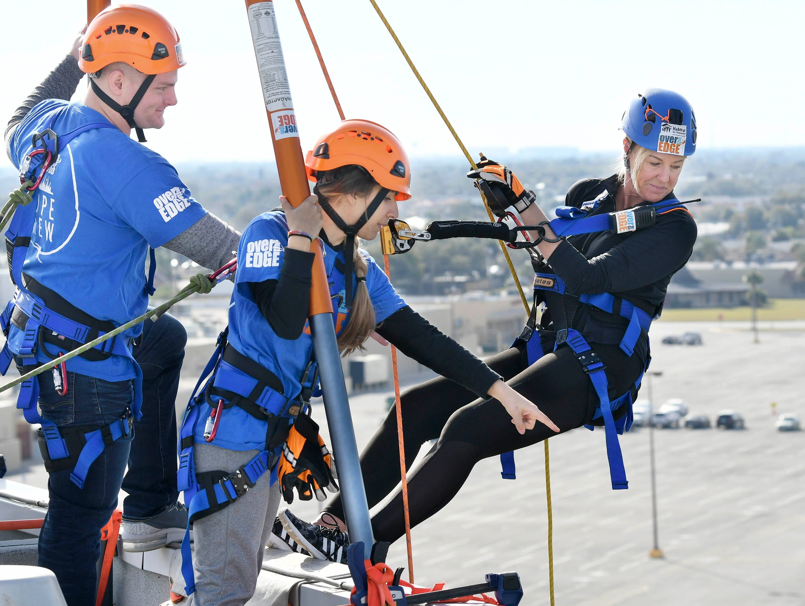 Cheryl Wadsworth prepares to go Over the Edge at the Melbourne Rialto Hilton on Saturday morning. Over the Edge is a fundraiser for Habitat Humanity of Brevard, an organization that helps low-income families buy affordable houses. Teams and individuals raised money for the chance to rappel eight stories down the Hilton.