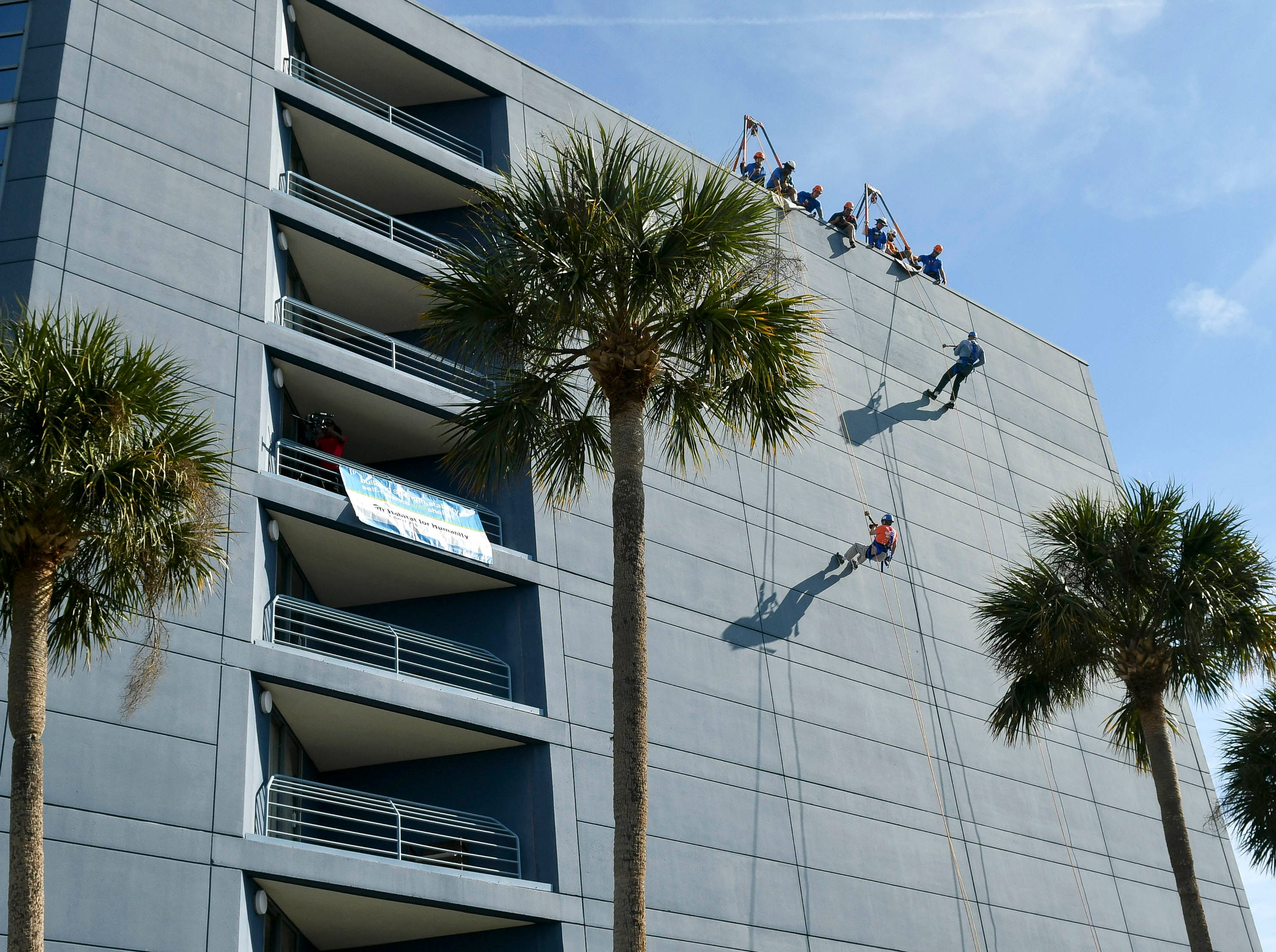 Participants in the Over the Edge fundraiser head down the side of the Melbourne Rialto Hilton on Saturday morning. Over the Edge is a fundraiser for Habitat Humanity of Brevard, an organization that helps low-income families buy affordable houses. Teams and individuals raised money for the chance to rappel eight stories down the Hilton.