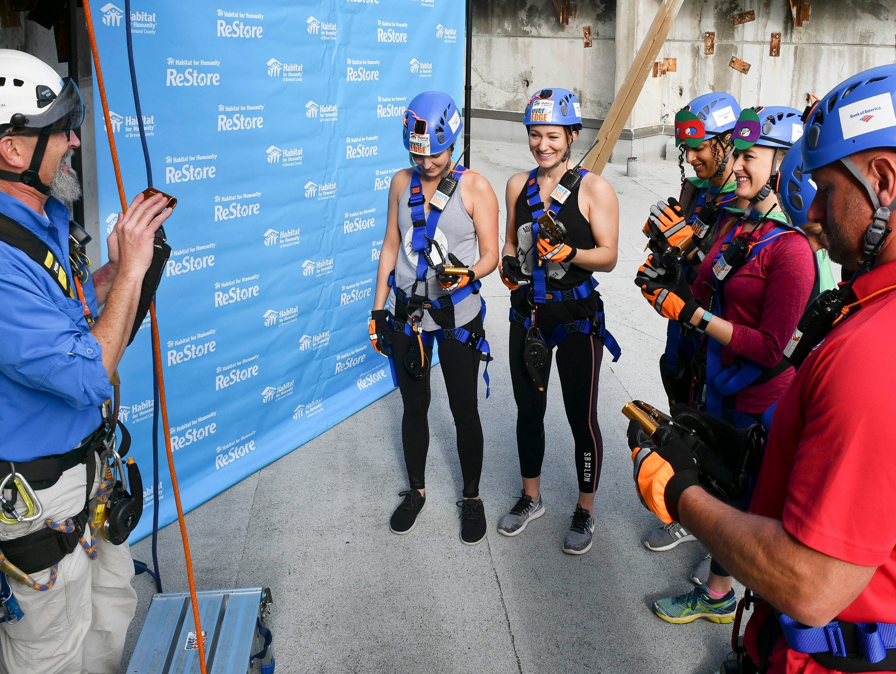 Jeff Martin instructs participants in how to use the ropes before they go Over the Edge at the Melbourne Rialto Hilton on Saturday morning. Over the Edge is a fundraiser for Habitat Humanity of Brevard, an organization that helps low-income families buy affordable houses. Teams and individuals raised money for the chance to rappel eight stories down the Hilton.