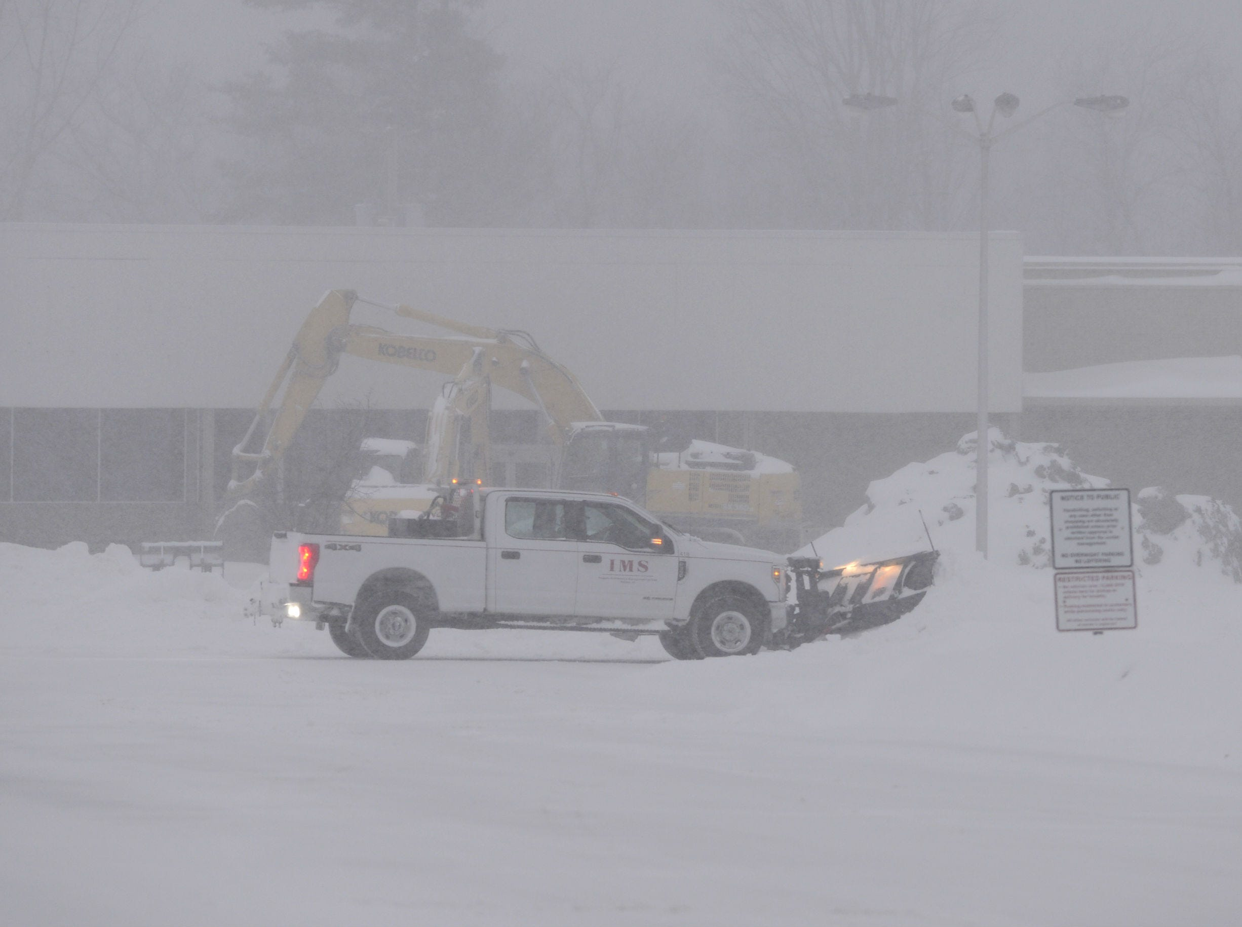 A snowplow works to clear parts of the parking lot at the former Kmart Plaza in South Burlington Sunday morning, Jan. 20, 2019. The winter storm, dubbed Harper by the Weather Channel, swept into Vermont Saturday night and was expected drop as much as 24 inches of snow by Sunday evening.
