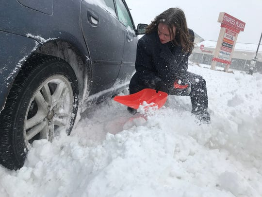 A motorist stuck in the snow plow bank entering Staples Plaza in South Burlington tries to shovel out on Sunday morning, Jan. 20, 2019, as Winter Storm Harper dumped snow across the region.