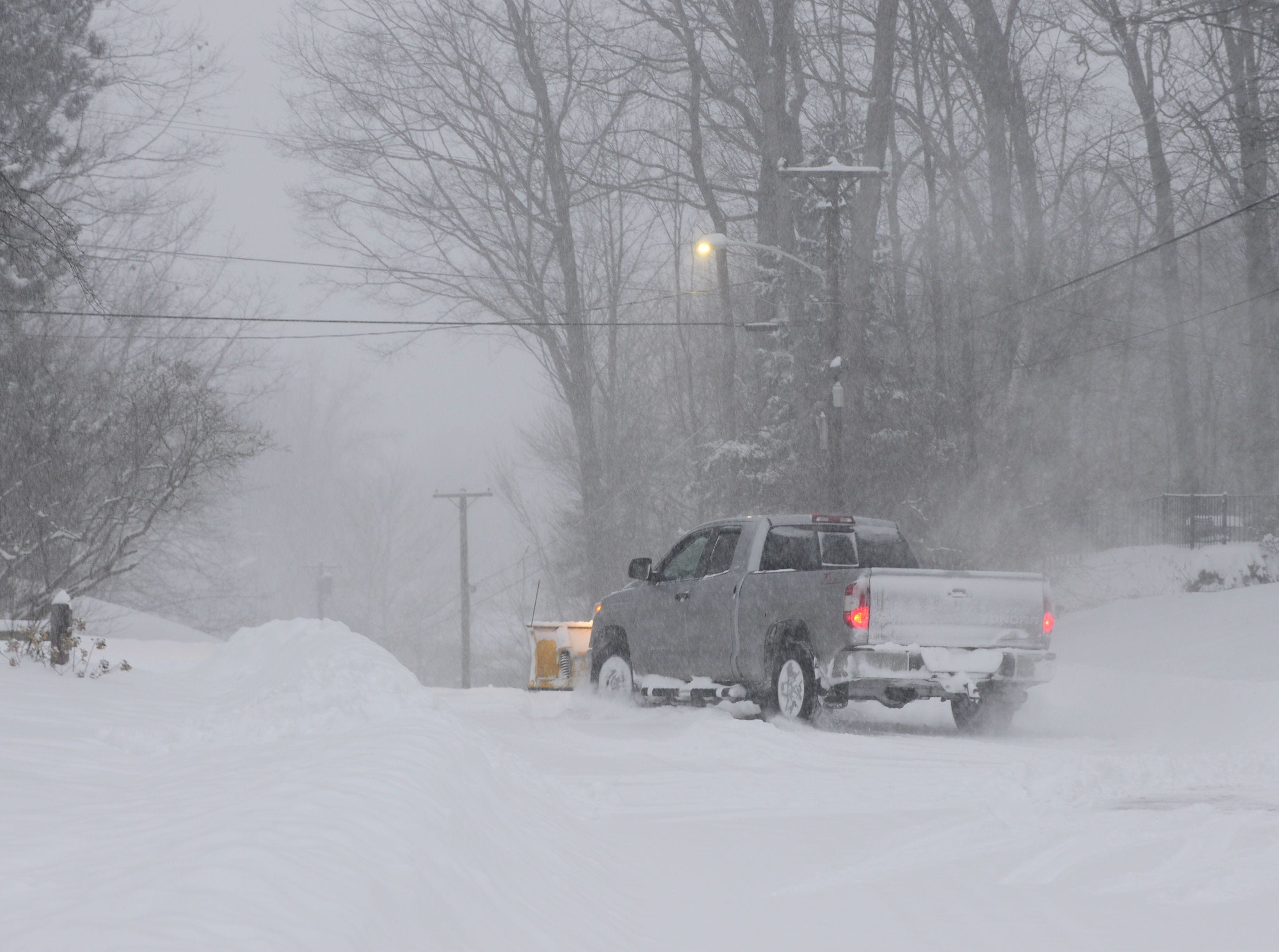 A snowplow heads down Brewer Parkway in South Burlington after clearing a driveway Sunday morning, Jan. 20, 2019. The winter storm, dubbed Harper by the Weather Channel, swept into Vermont Saturday night and was expected drop as much as 24 inches of snow by Sunday evening.