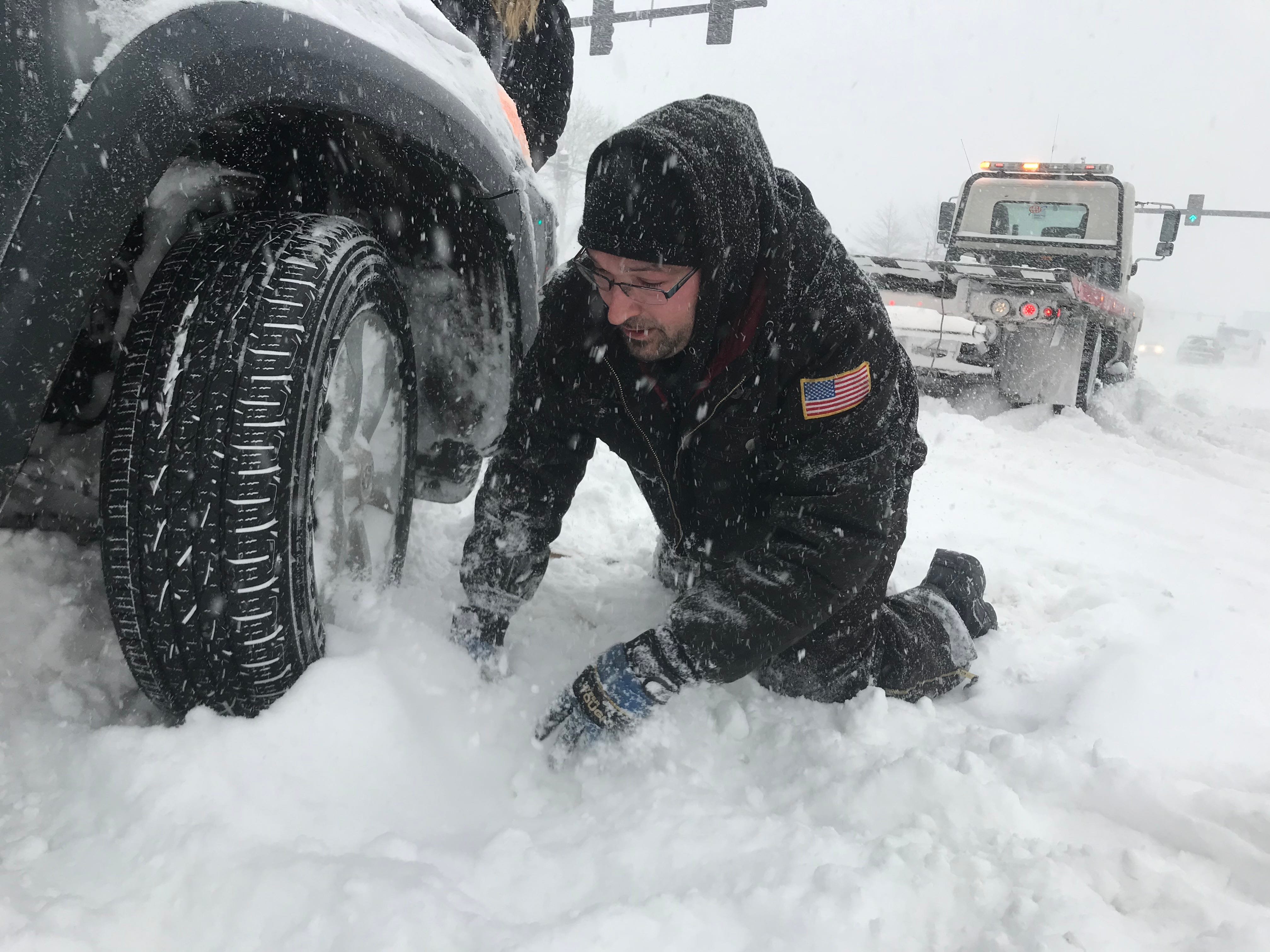 A Spillane's tow truck driver attaches a cable to a stuck vehicle on Main Street in Burlington, Vermont, after it got stuck on Sunday morning, Jan. 20, 2019.