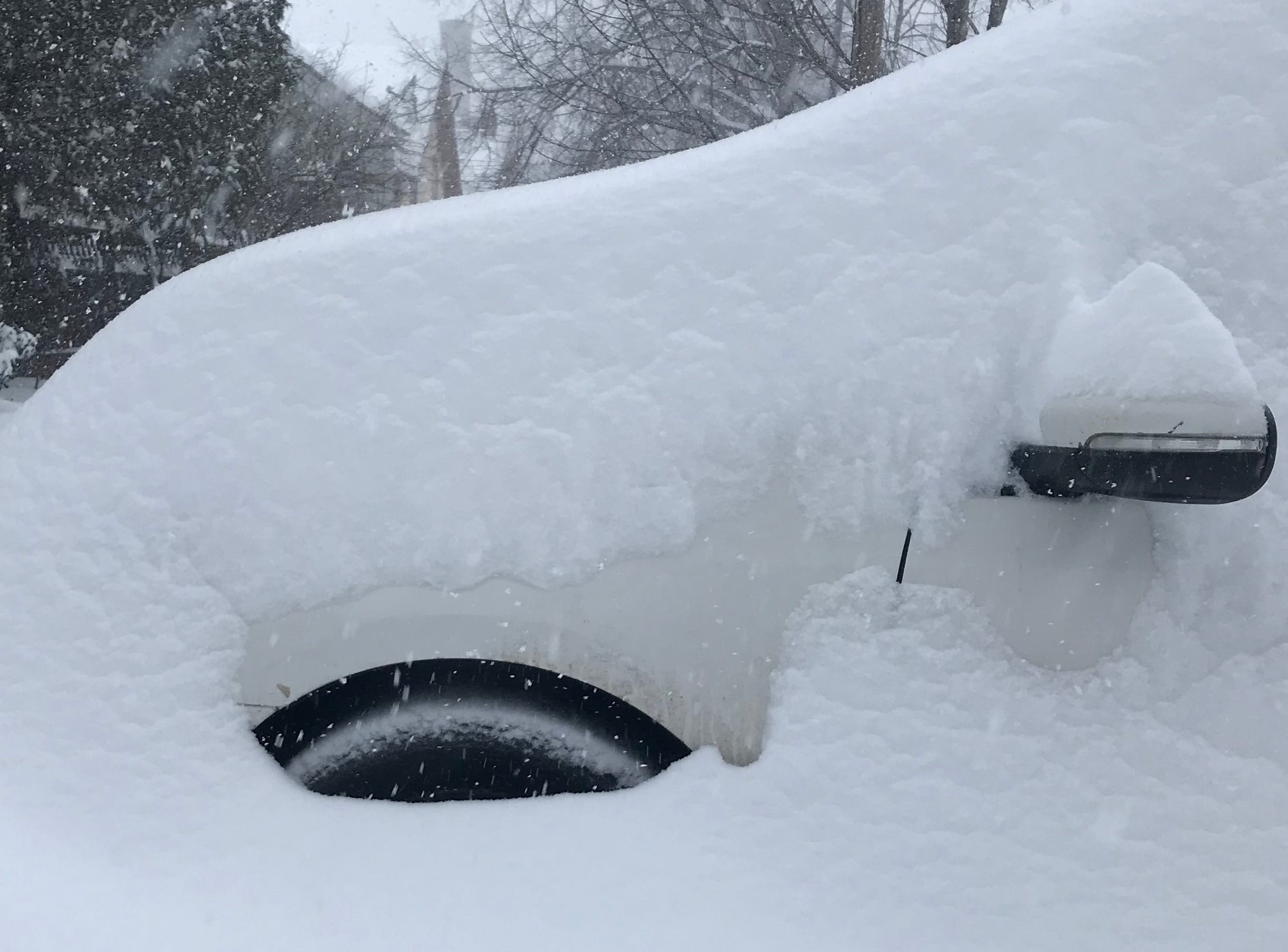 A car parked on St. Paul Street in Burlington, Vermont, sits under a blanket of snow on Sunday morning, Jan. 20, 2019.