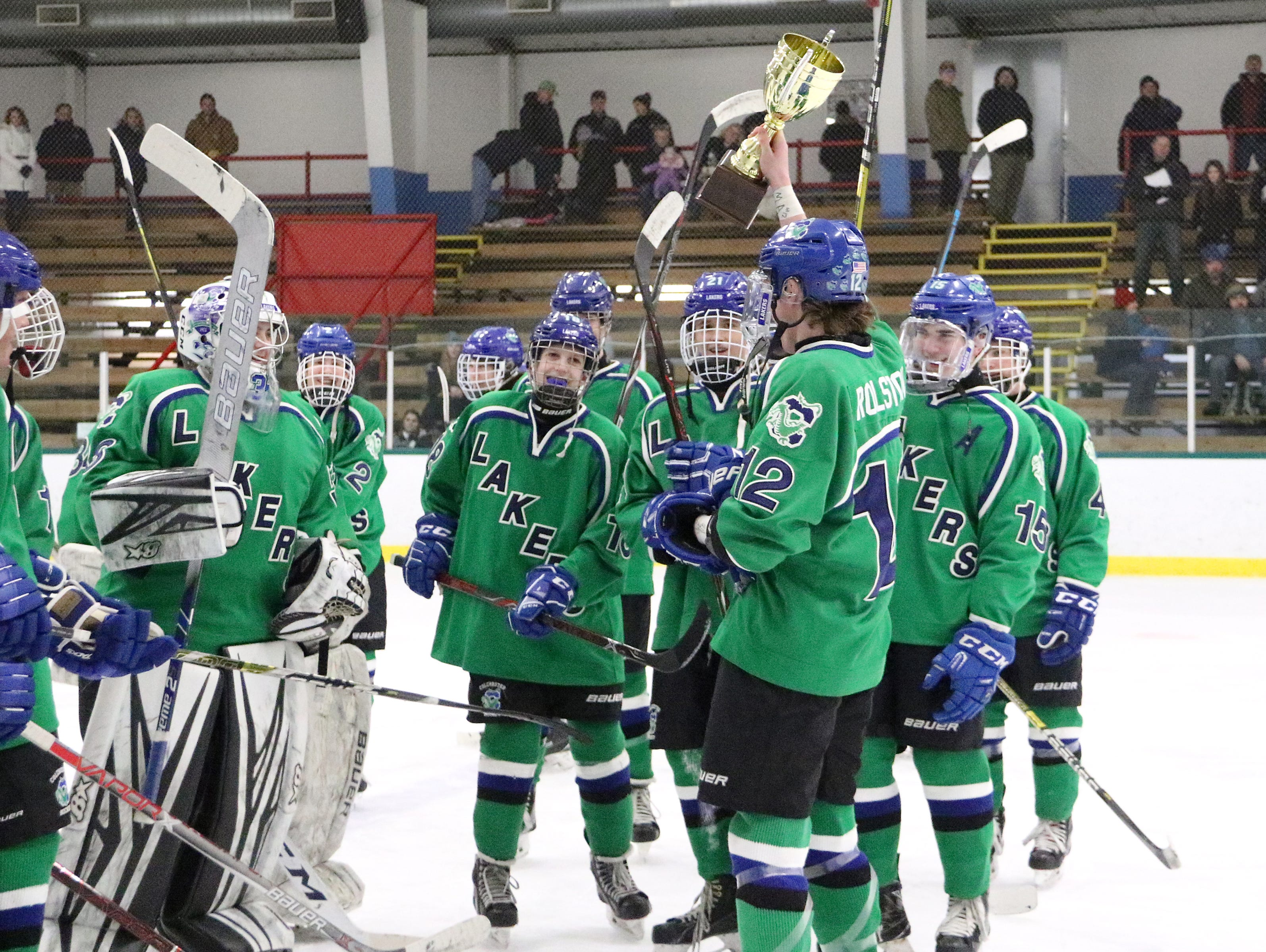 Senior Cam Rolston brings the BAHA Cup home to his teammates on Saturday at Leddy Arena. The senior netted two goals in the 6-0 win over Burlington.