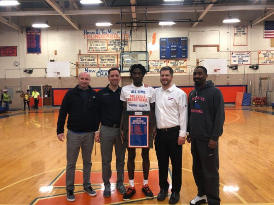 Millville's Rynell Lawrence (center) poses for a picture with coaches after breaking the school's all-time scoring record on Saturday against Kingsway. From left: Adam Carpenter, Mike LaTorre, Lawrence, Mike Jones and Reggie Hunter.
