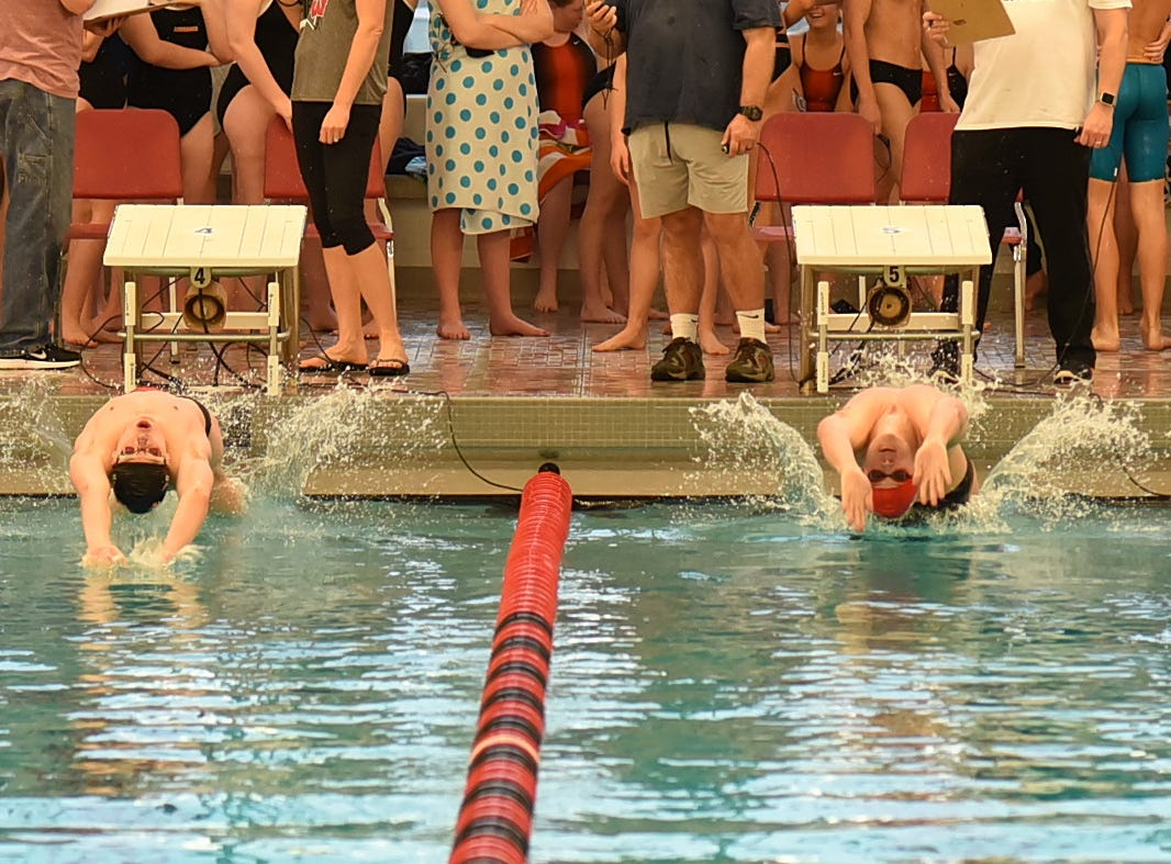 Brandon Day of Loveland and Michael Lorenz of Lakota West power off the wall to start the final heat of the boys 100 backstroke in the preliminaries at the Southwest Ohio Swimming and Diving Classic, January 19, 2019.
