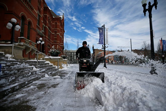 Ray Toepfert runs a snowblower as a crew clears the walkways in front of Music Hall ahead of tonight's Pops in Space performance in the Over-the-Rhine neighborhood of Cincinnati on Sunday, Jan. 20, 2019. Temperatures remain below 15 degrees with windchills as low as 4 in the region Sunday.