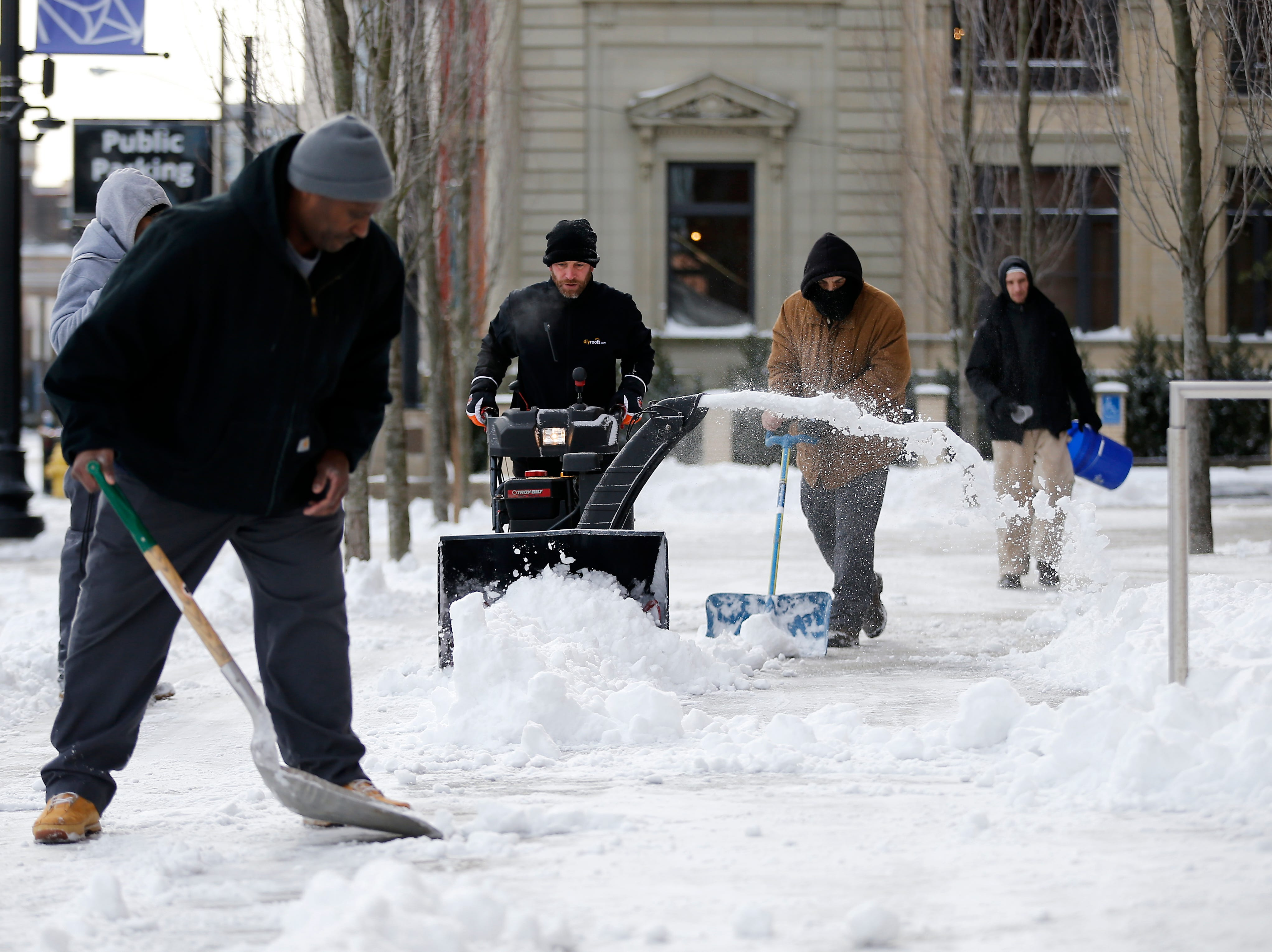 A crew works to crew the area in front of Music Hall ahead of tonight's Pops in Space show in the Over-the-Rhine neighborhood of Cincinnati on Sunday, Jan. 20, 2019. Temperatures remain below 15 degrees with windchills as low as 4 in the region Sunday.