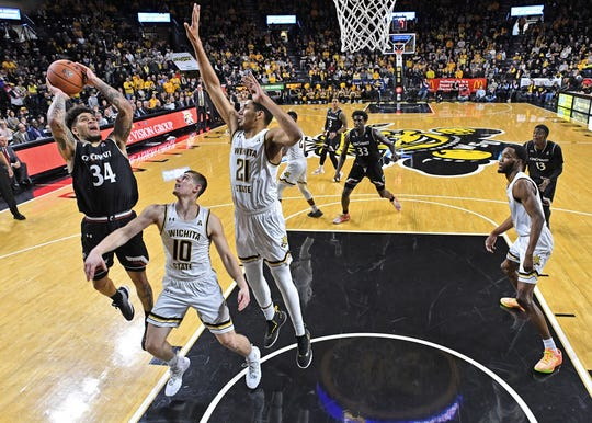 Cincinnati Bearcats guard Jarron Cumberland (34) puts up a shot against Wichita State Shockers guard Erik Stevenson (10) and forward Jaime Echenique (21) during the second half at Charles Koch Arena.