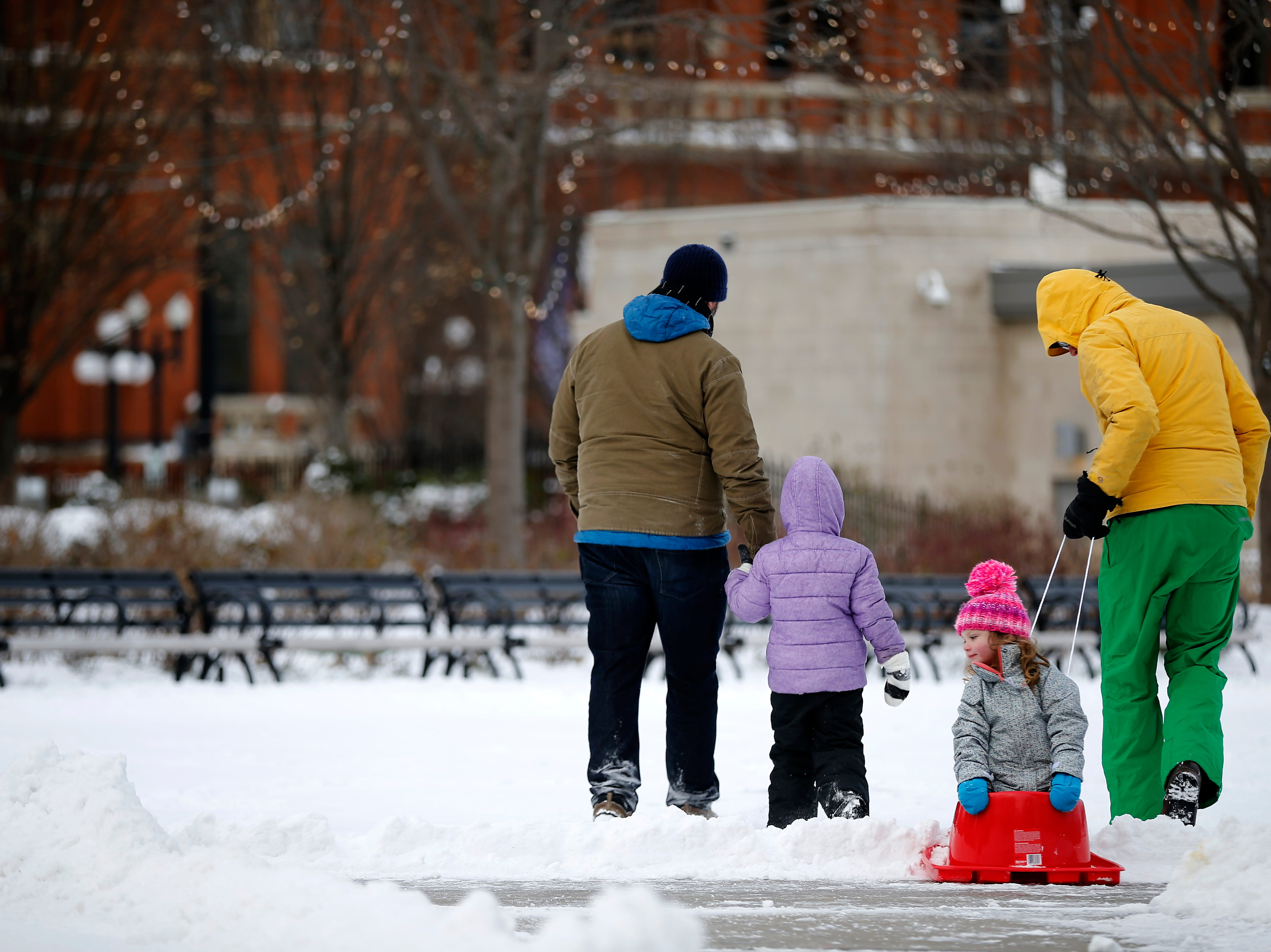 Henri Hudson, 3, trails behind as she's pulled on a sled by her father Scott Hudson, of Over-the-Rhine, as they head home after playing with Naomi Henderson, 5, and her dad Steve Smith at Washington Park in the Over-the-Rhine neighborhood of Cincinnati on Sunday, Jan. 20, 2019. Temperatures remain below 15 degrees with windchills as low as 4 in the region Sunday.