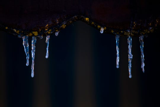 Ice hangs from a store front awning in Dayton, Ky., on Sunday, Jan. 20, 2019.