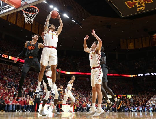 Iowa State guard Nick Weiler-Babb, center, pulls down a rebound as Oklahoma State guard Lindy Waters, left, defends during the first half of an NCAA college basketball game Saturday, Jan. 19, 2019, in Ames.