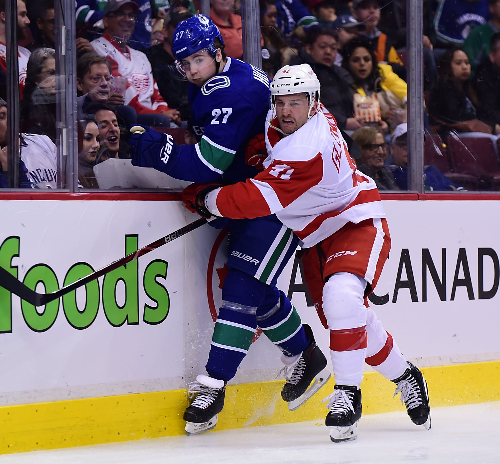 Red Wings forward Luke Glendening boards Canucks defenseman Ben Hutton during the second period on Sunday, Jan. 20, 2019, in Vancouver, British Columbia.
