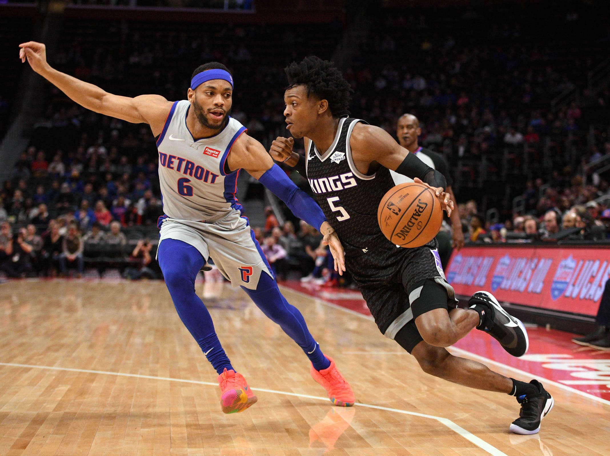 Sacramento Kings guard De'Aaron Fox (5) drives to the basket as Detroit Pistons guard Bruce Brown (6) defends during the first quarter at Little Caesars Arena.