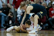 Ethan Happ (22) of the Wisconsin Badgers and Ignas Brazdeikis (13) of the Michigan Wolverines battle for a loose ball in the second half Saturday.