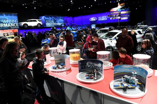 People can build Lego figures at the Ford display at the North American International Auto Show at Cobo Center in Detroit on Jan. 20, 2019.