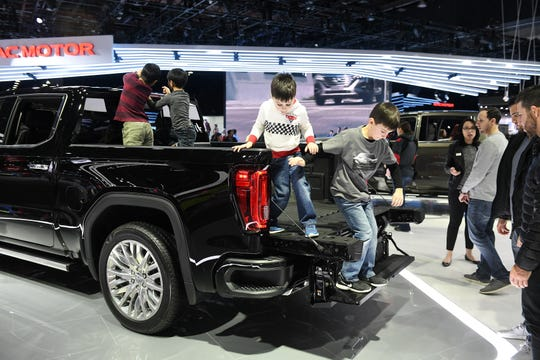 Cristiano Vittorini, 5, left, and his brother, Valentino Vittorini, 6, of Rochester Hills climb out of the bed of a Denali using the GMC multi-pro tail gate at the North American International Auto Show at Cobo Center in Detroit on Jan. 20, 2019.