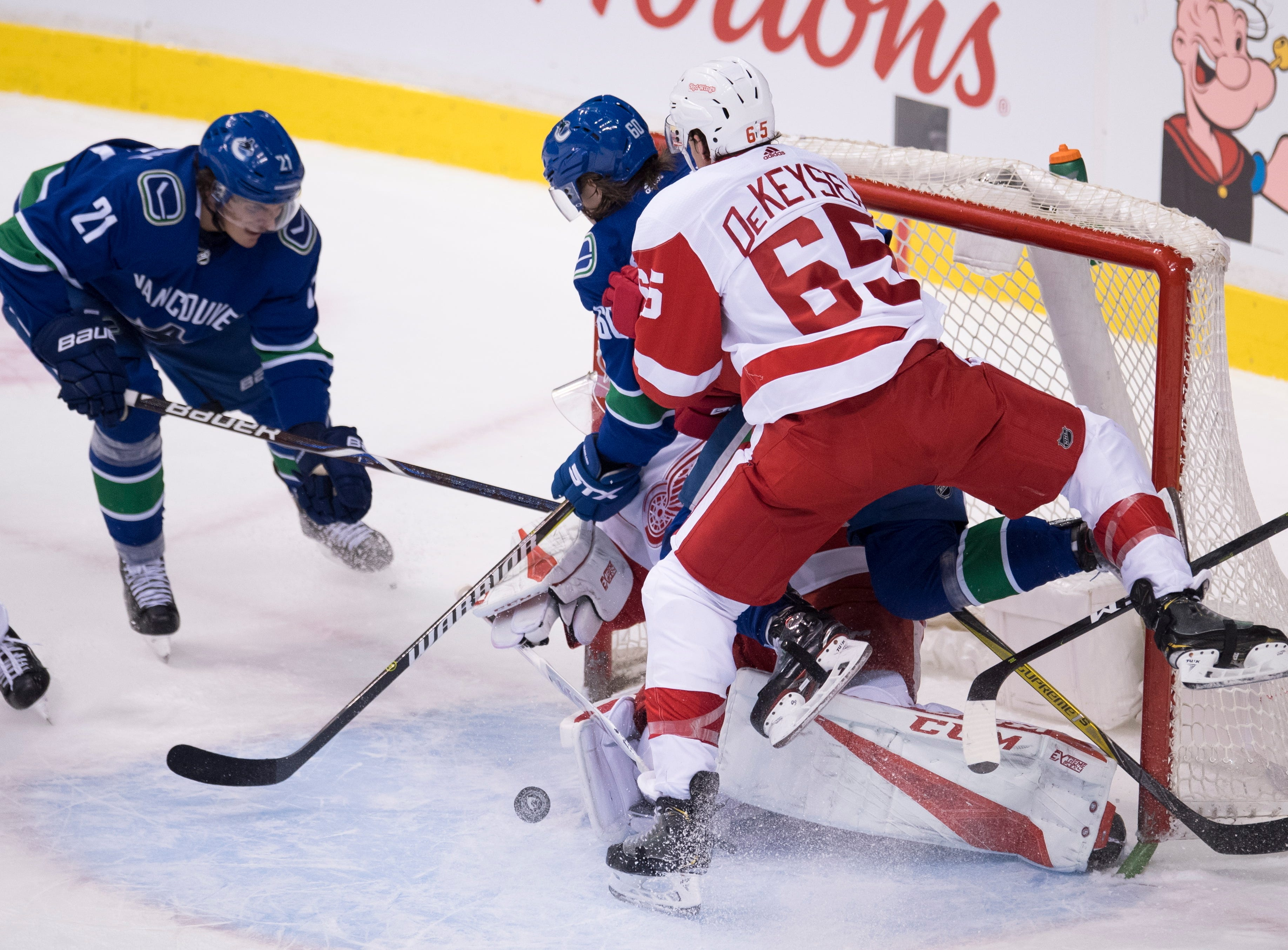 Vancouver Canucks left wing Loui Eriksson (21) looks on as Detroit Red Wings defenseman Danny DeKeyser (65) tries to stop Canucks center Markus Granlund (60) from getting a shot on Red Wings goaltender Jonathan Bernier (45) during the second-period.