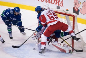 Vancouver Canucks left wing Loui Eriksson (21) looks on as Detroit Red Wings defenseman Danny DeKeyser (65) tries to stop Canucks center Markus Granlund (60) from getting a shot on Red Wings goaltender Jonathan Bernier (45) during the second period.