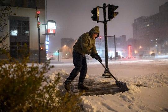 Larry Donald battles the wind as he shovels the sidewalk in front of The Plaza Downtown condominiums building on the corner of Locust and Southeast Third Streets in downtown Evansville, Saturday, Jan. 19, 2019.