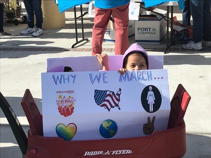 Jacquelyn Cote, 4, of St. James City, peeks over the signage on a wagon pulled by her mom Nancy Cote at the Women's March Fort Myers in Centennial Park downtown.