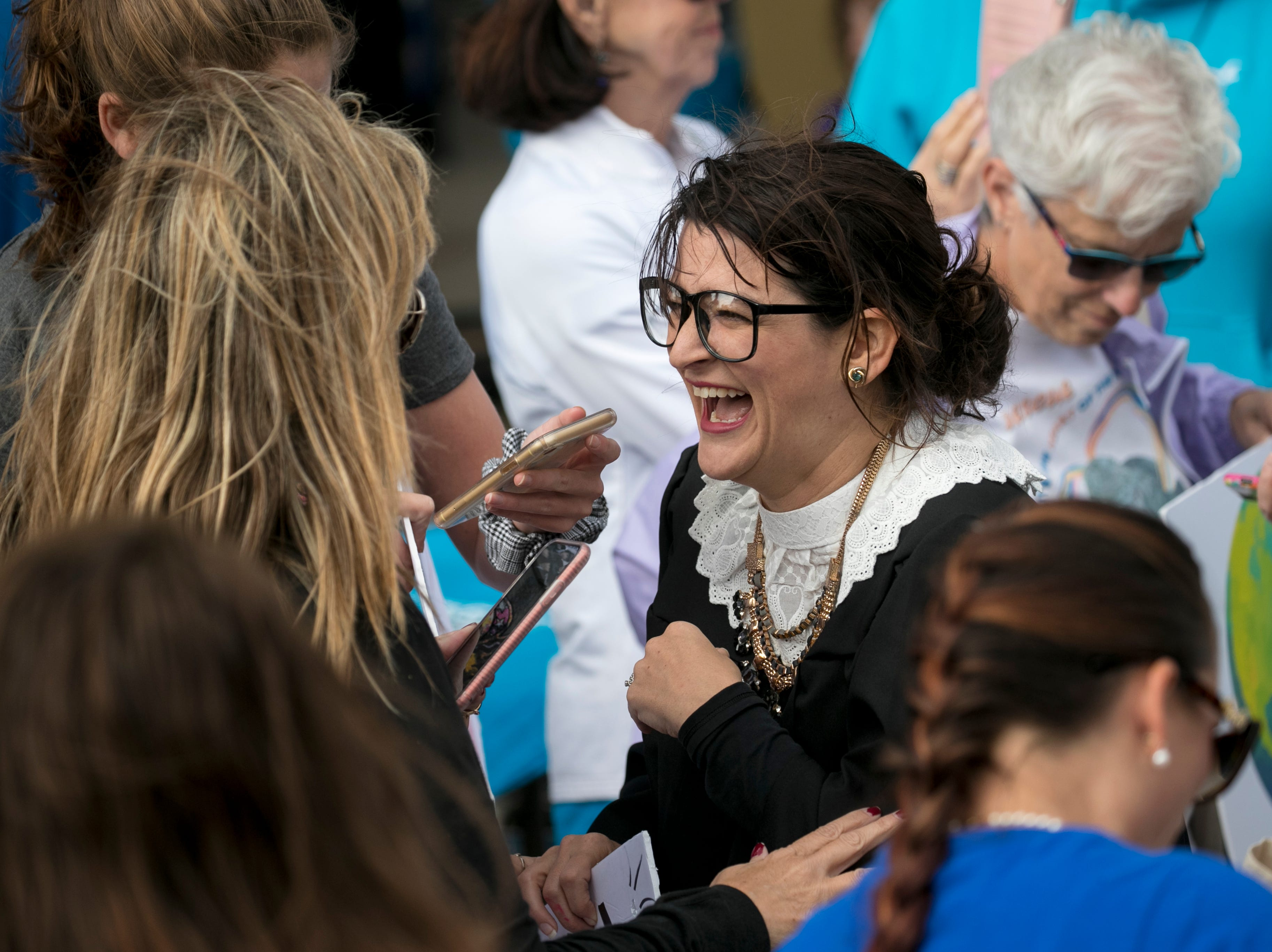 Jessica Lindsey, dressed as Supreme Court Justice Ruth Bader Ginsberg, laughs with other participants in the Fort Myers Women's March on Sunday, Jan. 20, 2019.