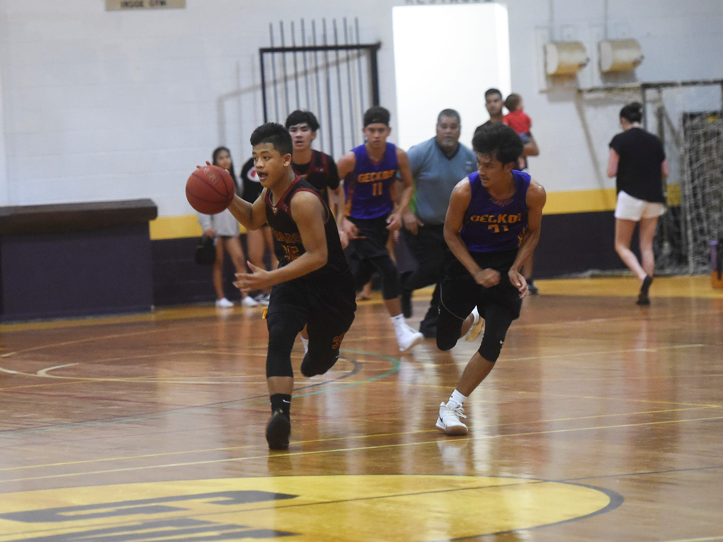 Father Duenas' Elijah Garrido handles the ball on a fast break against the George Washington Geckos during their Independent Interscholastic Athletic Association of Guam Boys' Basketball game at the GW High School gym, Jan. 19, 2019. The Friars came through with a 52-69 comeback victory over the Geckos after trailing in the first half.