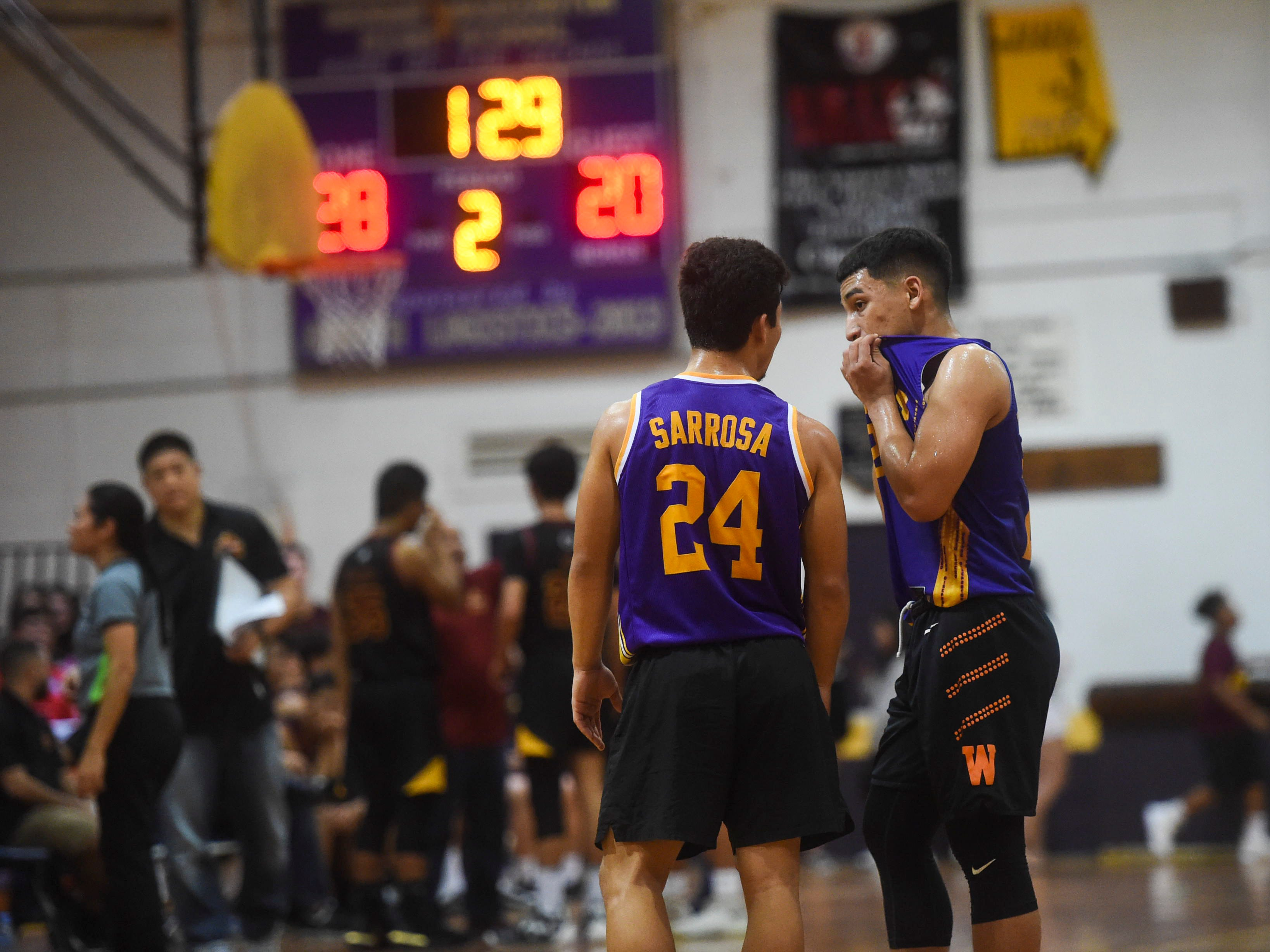 George Washington Geckos teammates talk during a break in their Independent Interscholastic Athletic Association of Guam Boys' Basketball game against the Father Duenas Friars at the GW High School gym, Jan. 19, 2019. The Friars came through with a 52-69 comeback victory over the Geckos after trailing in the first half.