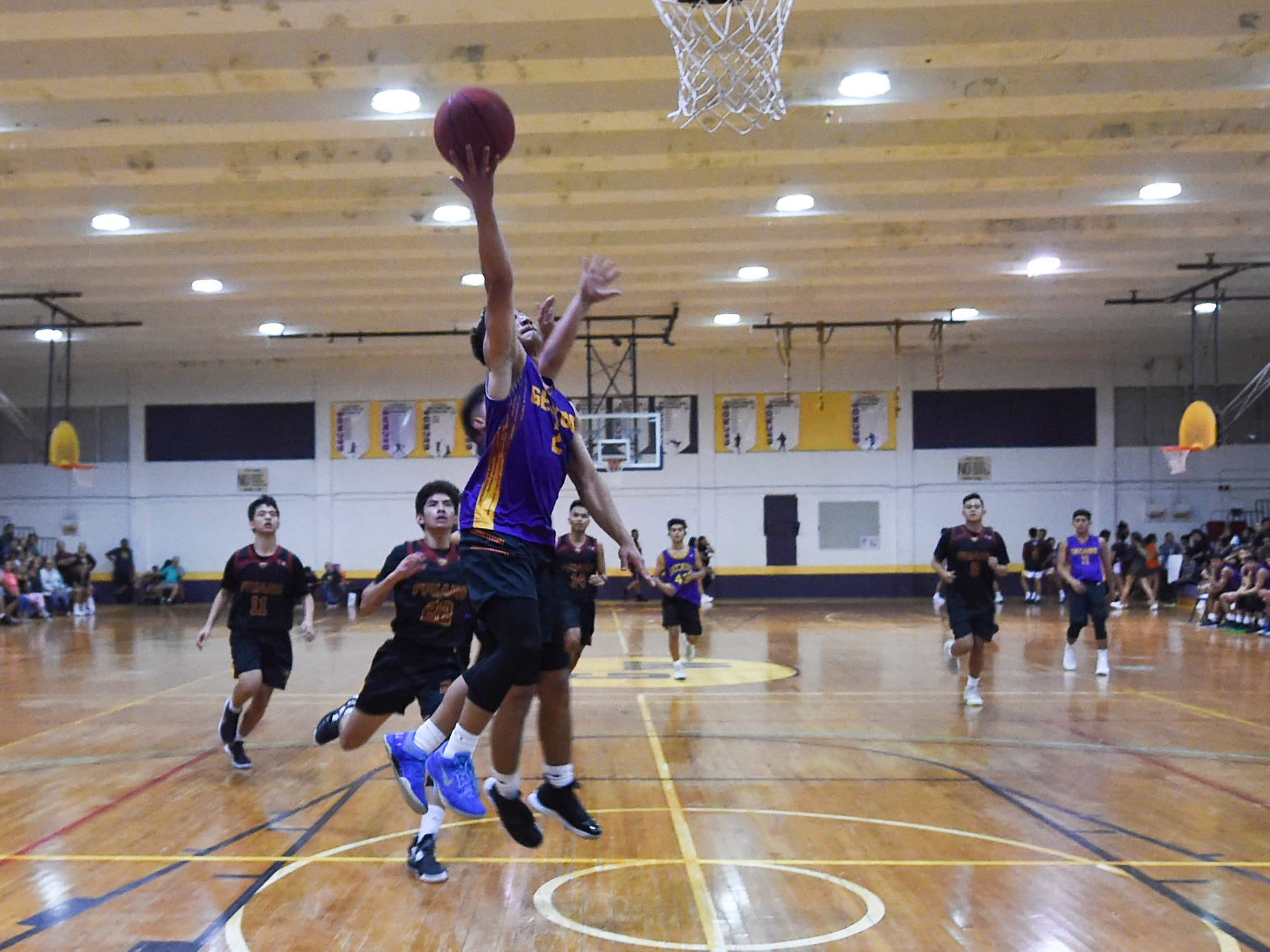 George Washington's Dylan Trusso (2) skies for a layup on a fast break against the Father Duenas Friars during their Independent Interscholastic Athletic Association of Guam Boys' Basketball game at the GW High School gym, Jan. 19, 2019. The Friars came through with a 52-69 comeback victory over the Geckos after trailing in the first half.