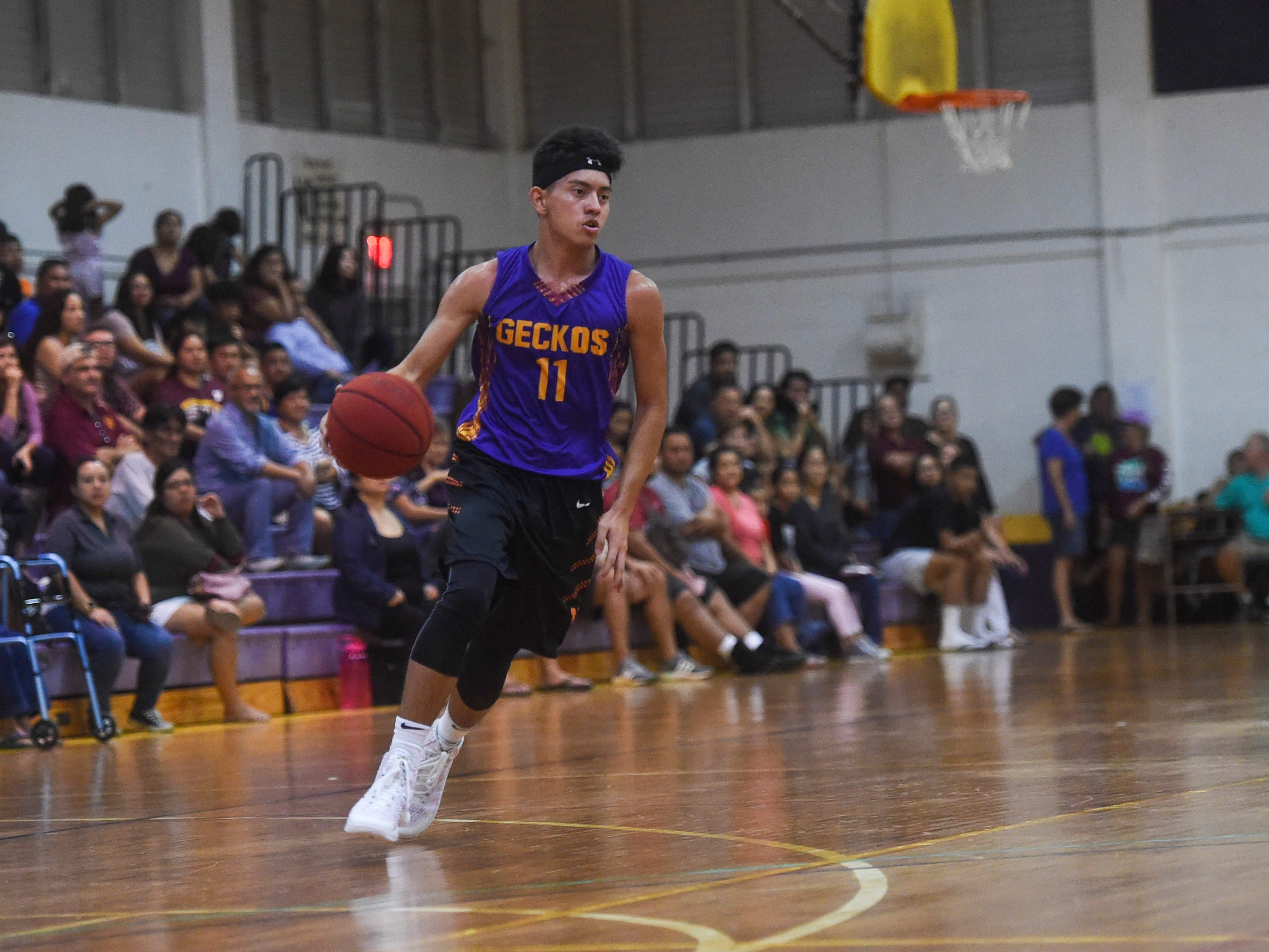 George Washington player Ricky Macias (11) handles the ball during an Independent Interscholastic Athletic Association of Guam Boys' Basketball game against the Father Duenas Friars at the GW High School gym, Jan. 19, 2019. The Friars came through with a 52-69 comeback victory over the Geckos after trailing in the first half.
