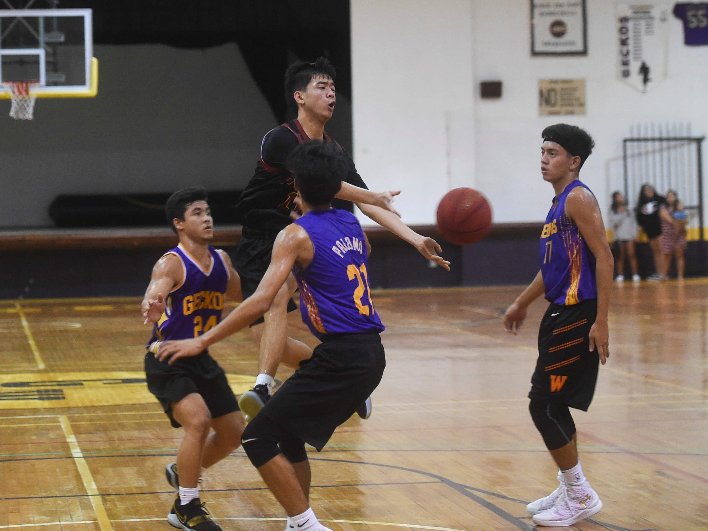 Father Duenas' Colin Santiago (11) passes out of a double team against the George Washington Geckos during their Independent Interscholastic Athletic Association of Guam Boys' Basketball game at the GW High School gym, Jan. 19, 2019. The Friars came through with a 52-69 comeback victory over the Geckos after trailing in the first half.