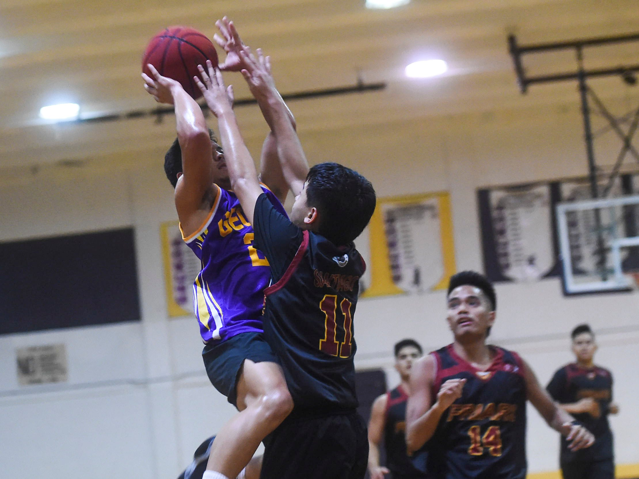 George Washington guard Shelby Meeks attempts a shot over Father Duenas' Colin Santiago (11) during their Independent Interscholastic Athletic Association of Guam Boys' Basketball game at the GW High School gym, Jan. 19, 2019. The Friars came through with a 52-69 comeback victory over the Geckos after trailing in the first half.