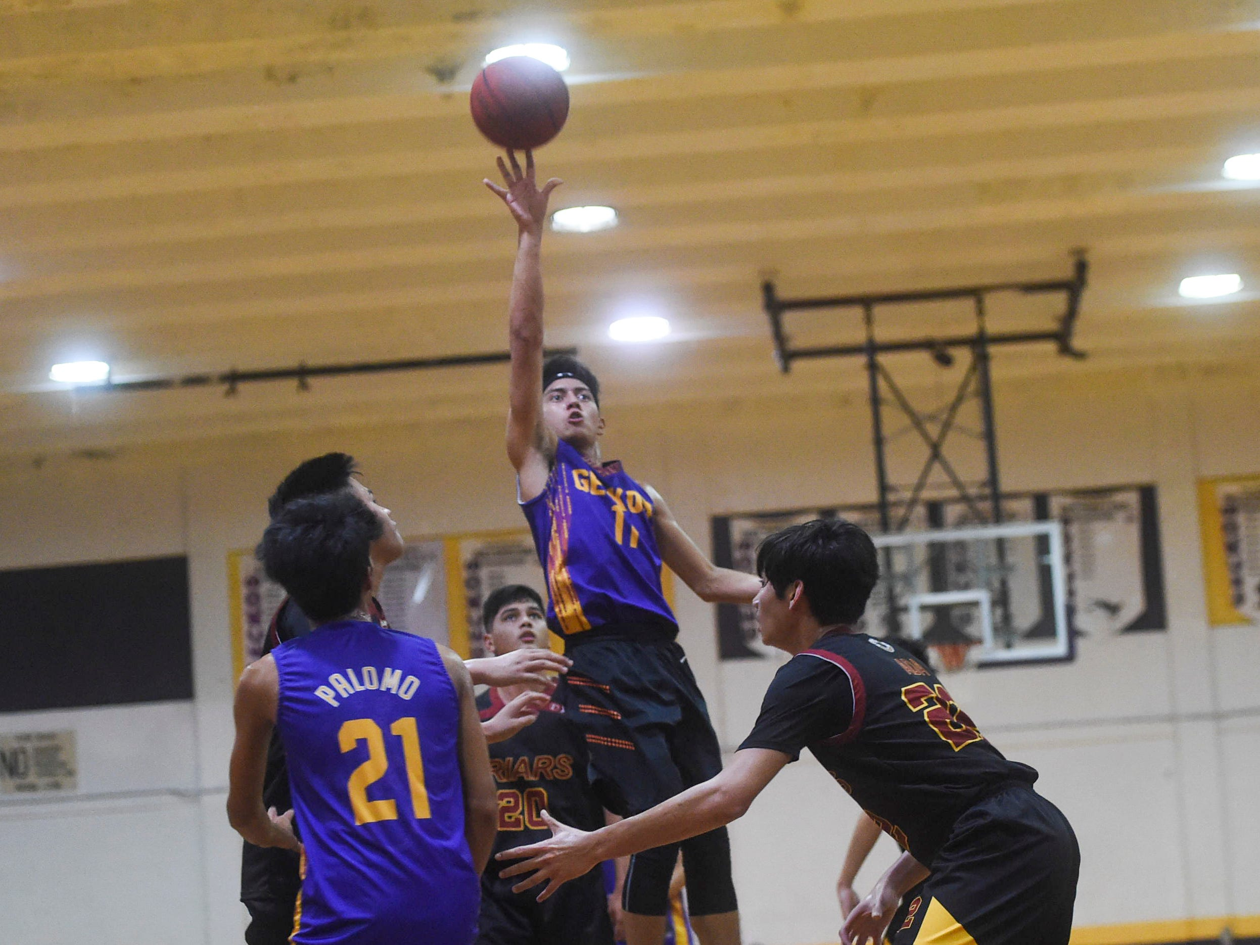 George Washington's Ricky Macias (11) attempts a floater against the Friars during their Independent Interscholastic Athletic Association of Guam Boys' Basketball game at the GW High School gym, Jan. 19, 2019. The Friars came through with a 52-69 comeback victory over the Geckos after trailing in the first half.