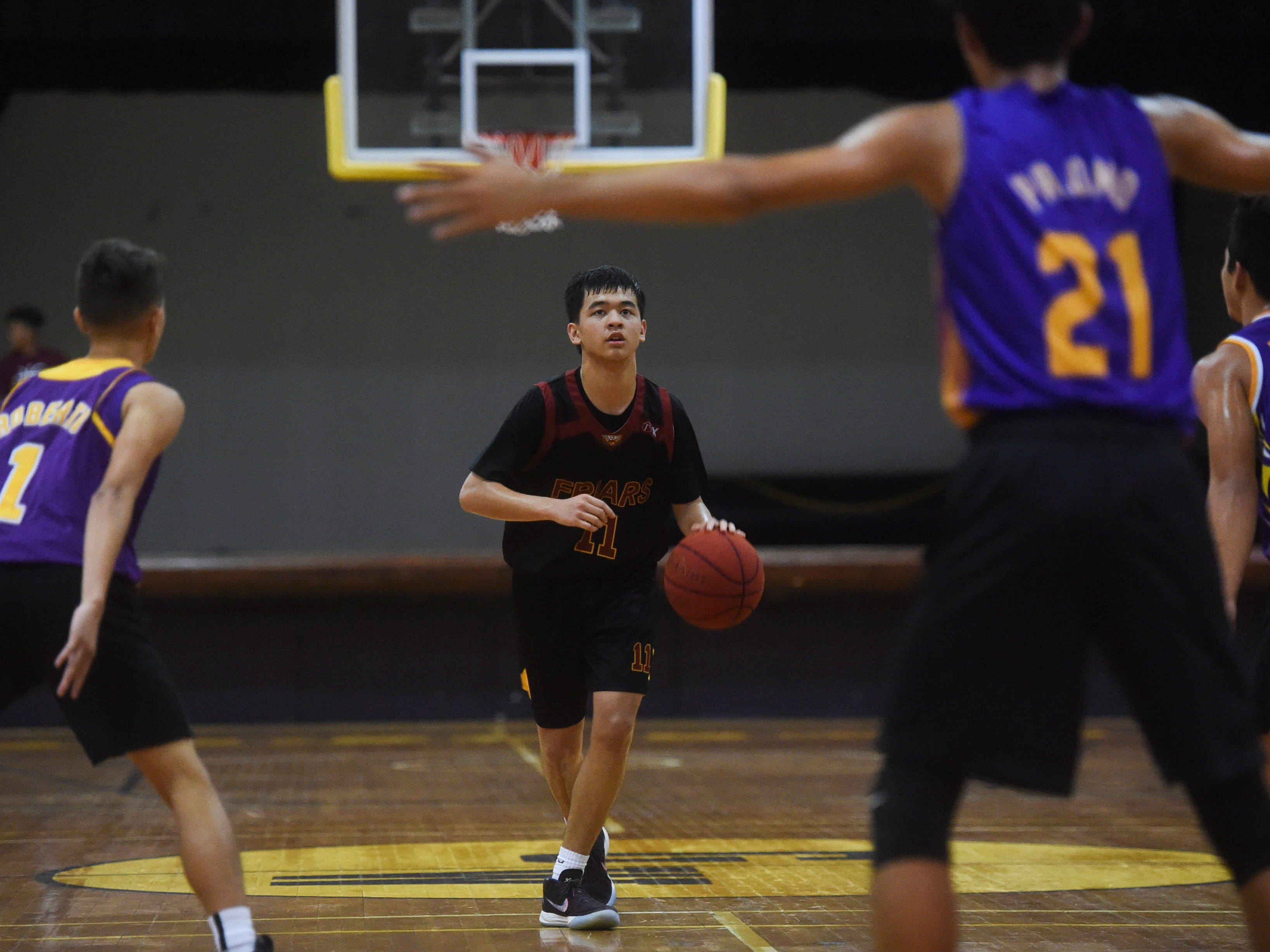 Father Duenas' Colin Santiago (11) brings the ball down against the George Washington Geckos during their Independent Interscholastic Athletic Association of Guam Boys' Basketball game at the GW High School gym, Jan. 19, 2019. The Friars came through with a 52-69 comeback victory over the Geckos after trailing in the first half.