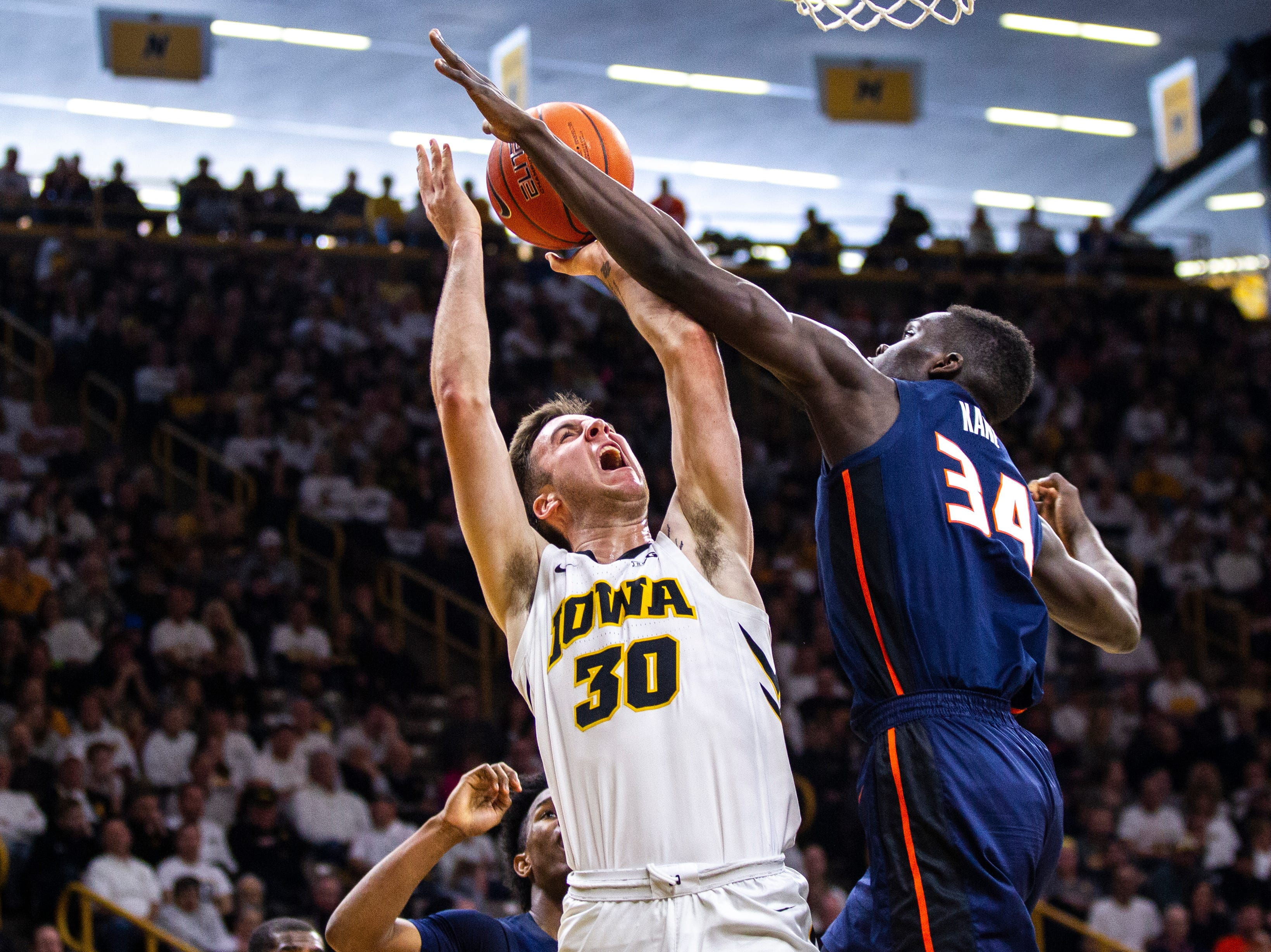 Illinois' Samba Kane (34) blocks Iowa guard Connor McCaffery (30) during a NCAA Big Ten Conference men's basketball game on Sunday, Jan. 20, 2019, at Carver-Hawkeye Arena in Iowa City, Iowa.
