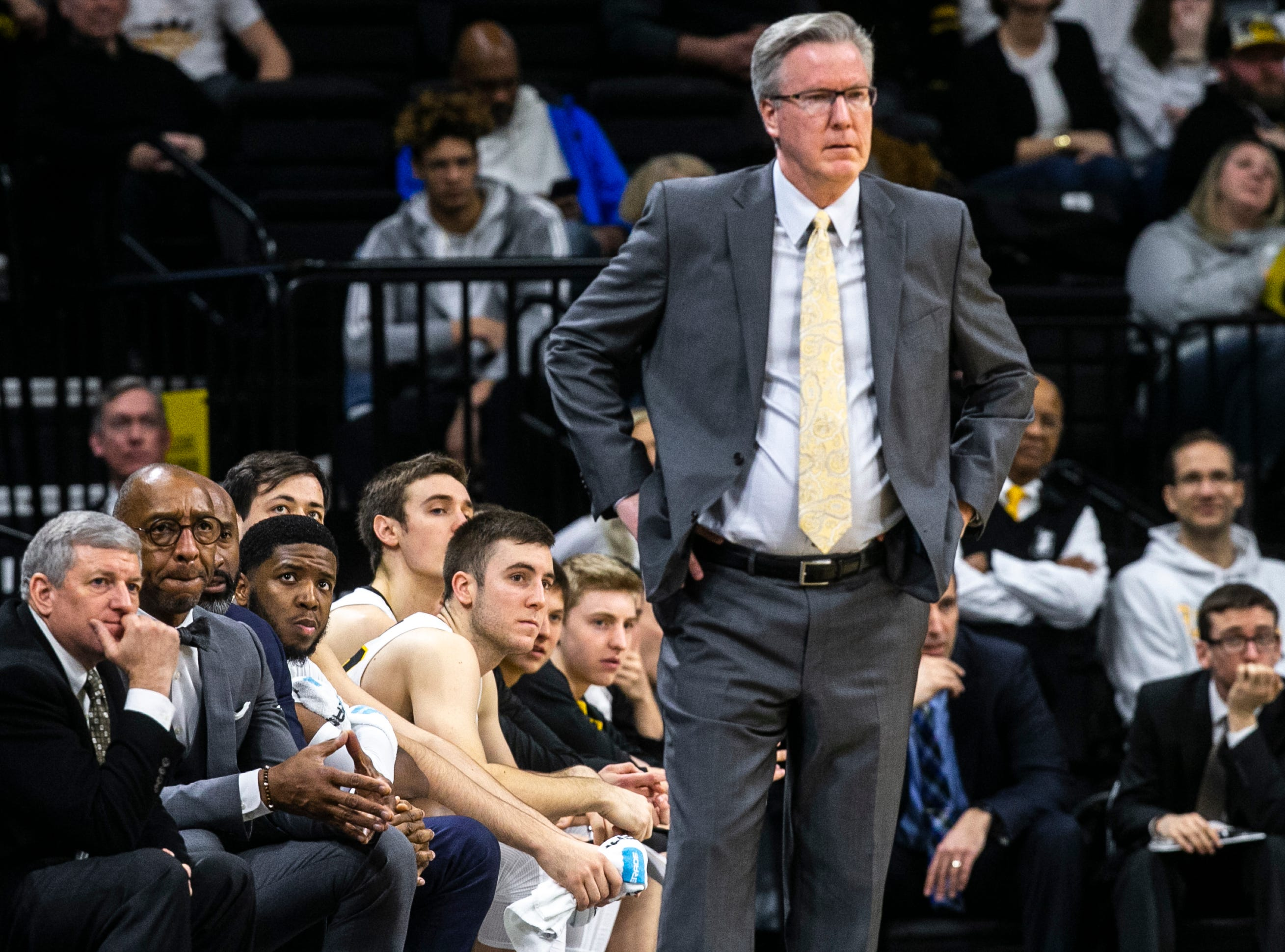 Iowa guard Isaiah Moss (third from left) looks on from the bench while Iowa men's basketball head coach Fran McCaffery stands along the baseline during a NCAA Big Ten Conference men's basketball game on Sunday, Jan. 20, 2019, at Carver-Hawkeye Arena in Iowa City, Iowa.