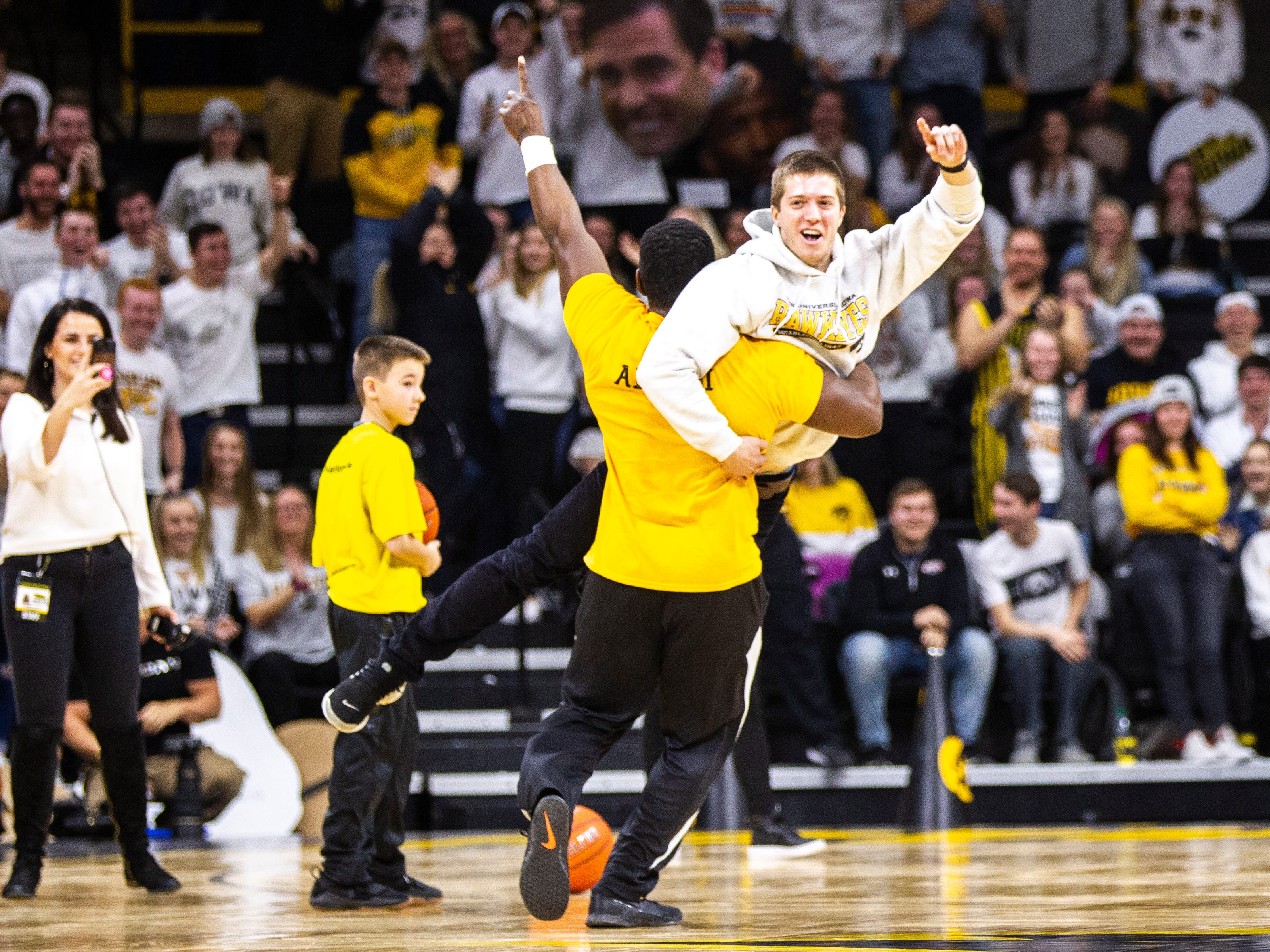 University of Iowa student Eric Huber is embraced by alumni  spirit squad member Oz Agbese after making a half-court shot during a NCAA Big Ten Conference men's basketball game on Sunday, Jan. 20, 2019, at Carver-Hawkeye Arena in Iowa City, Iowa.