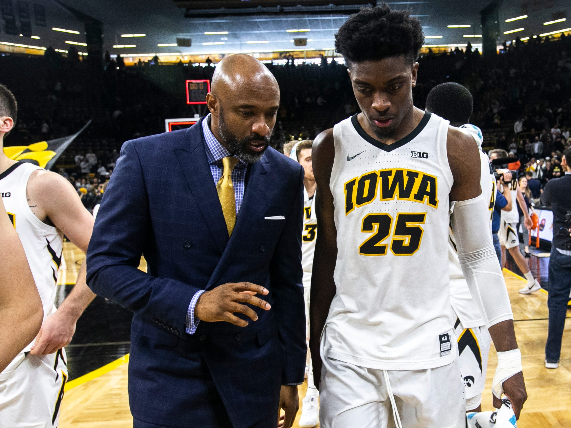 Iowa assistant coach Andrew Francis, left, talks with Iowa forward Tyler Cook (25) after a NCAA Big Ten Conference men's basketball game on Sunday, Jan. 20, 2019, at Carver-Hawkeye Arena in Iowa City, Iowa. The Hawkeyes defeated the Fighting Illini, 95-71.